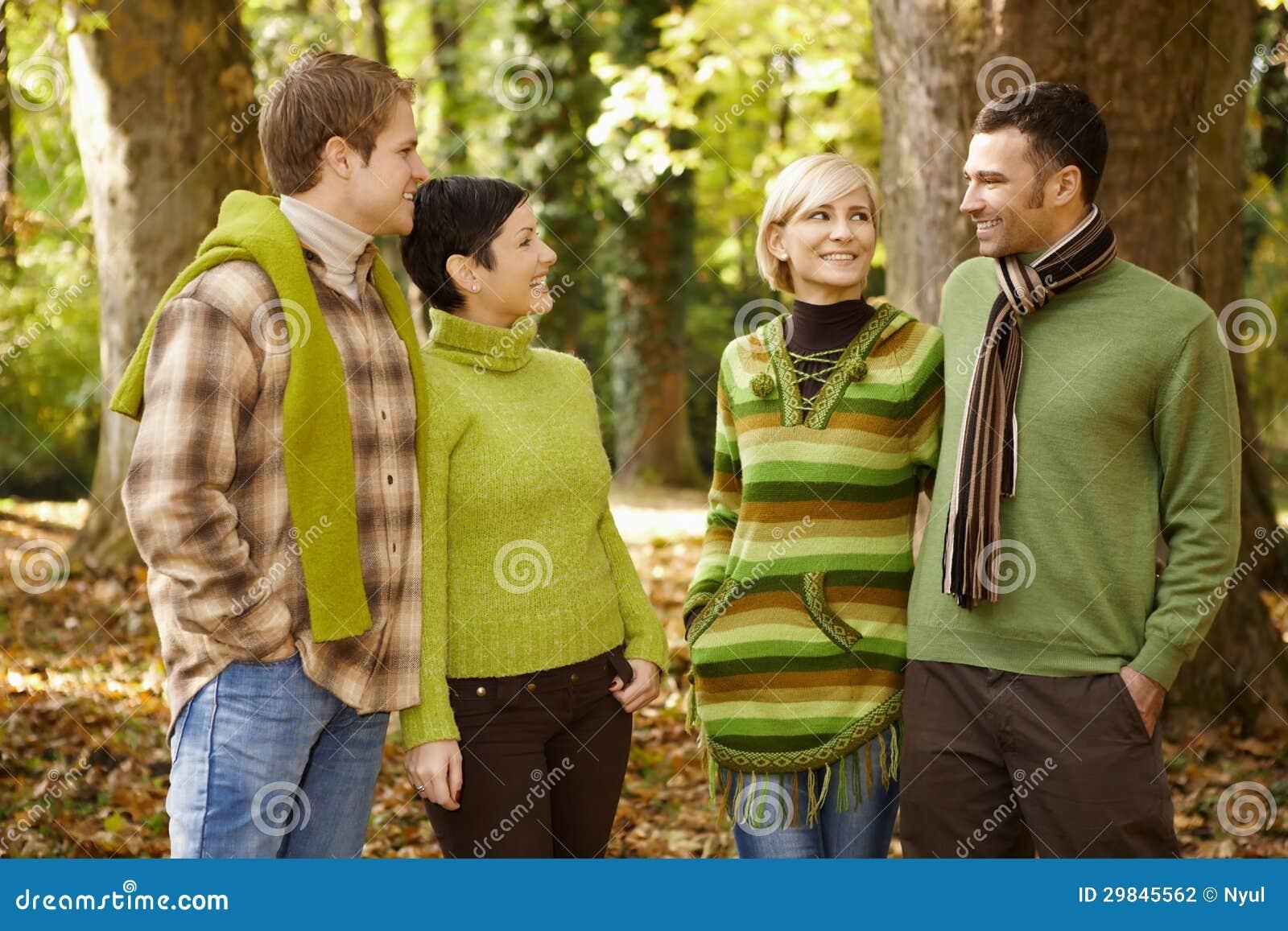 Dois pares que falam na floresta do outono
