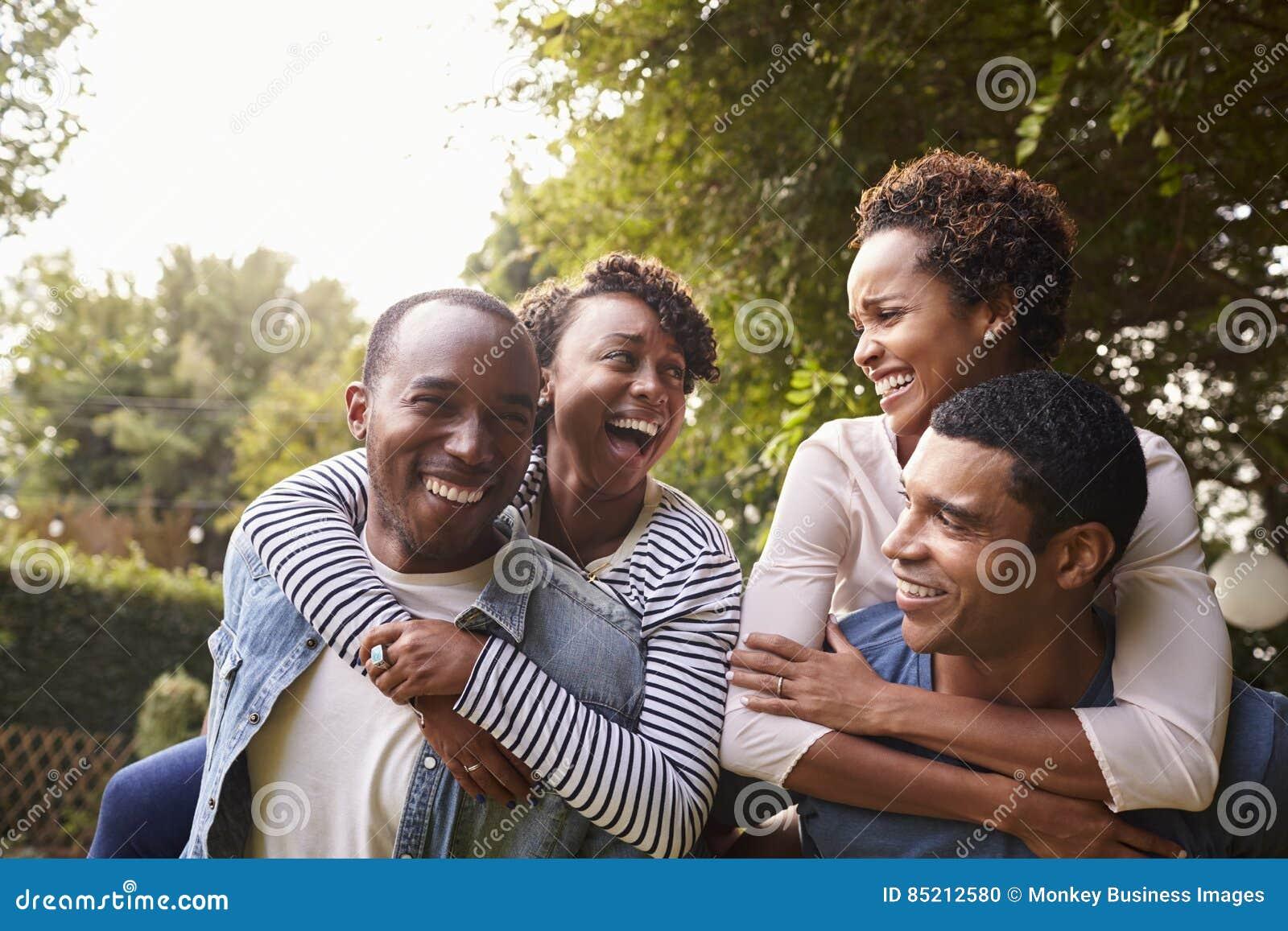 Dois pares pretos adultos novos que têm o reboque do divertimento