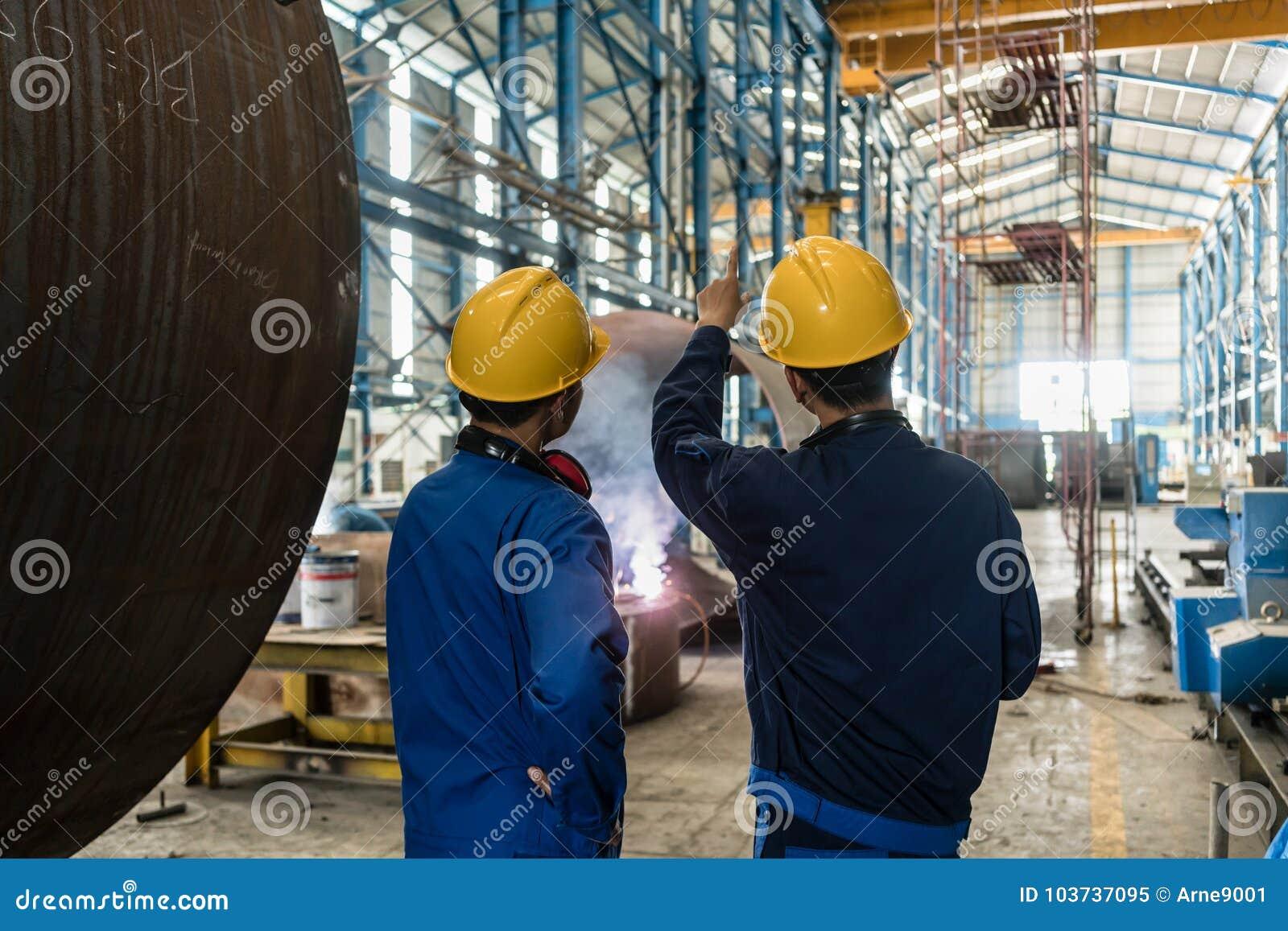 Dois peritos asiáticos que falam ao supervisionar a fabricação