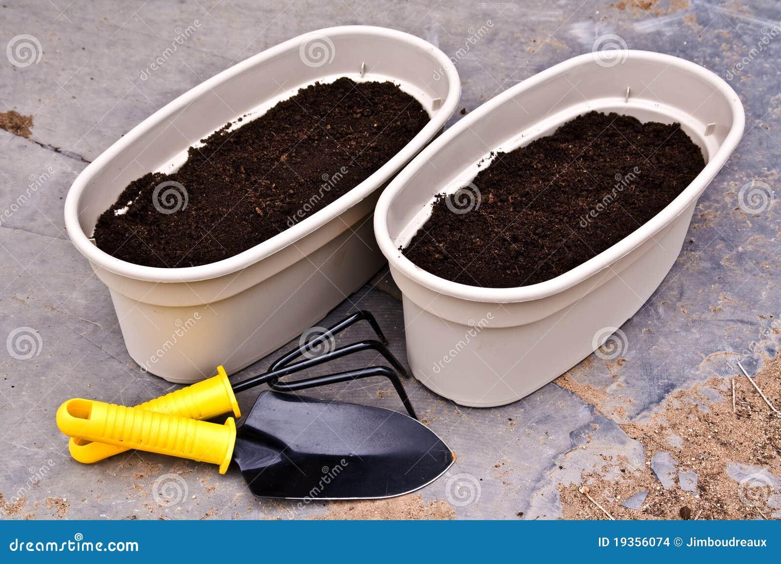 Dois plantadores e ferramentas de jardim