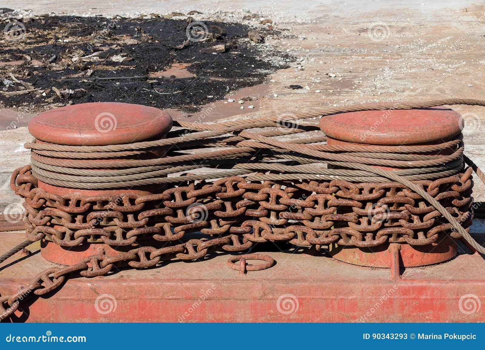 Dois postes de amarração do metal com correntes e cabos oxidados