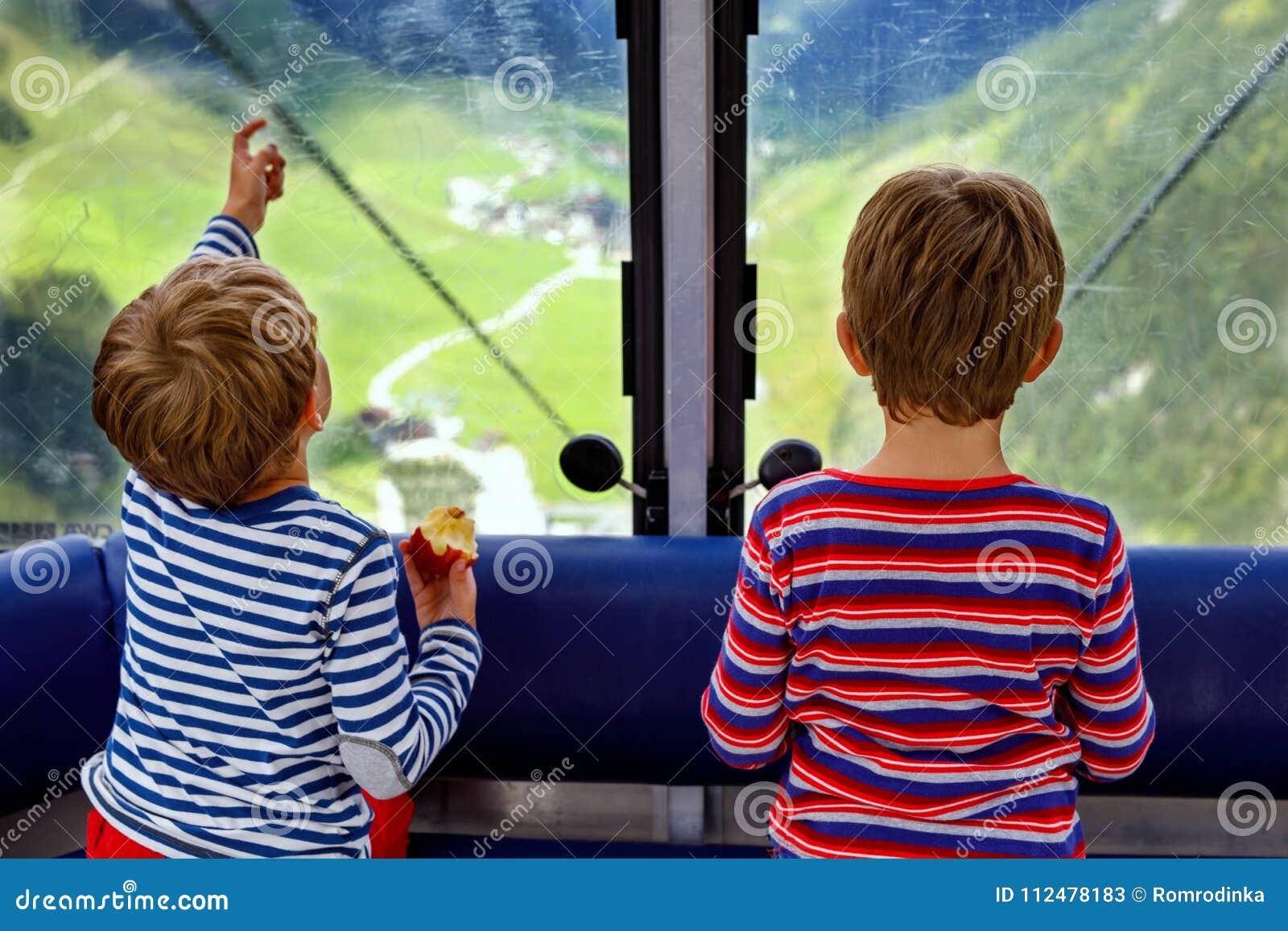 Dois rapazes pequenos que sentam-se dentro da cabine do teleférico e que olham em montanhas ajardinam