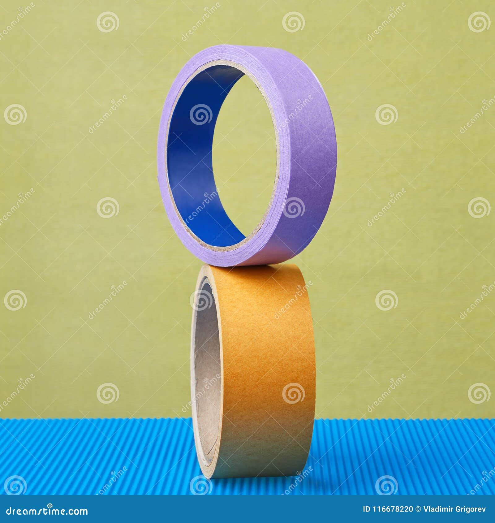 Dois rolos da fita pegajosa colorem o equilíbrio no fundo roxo