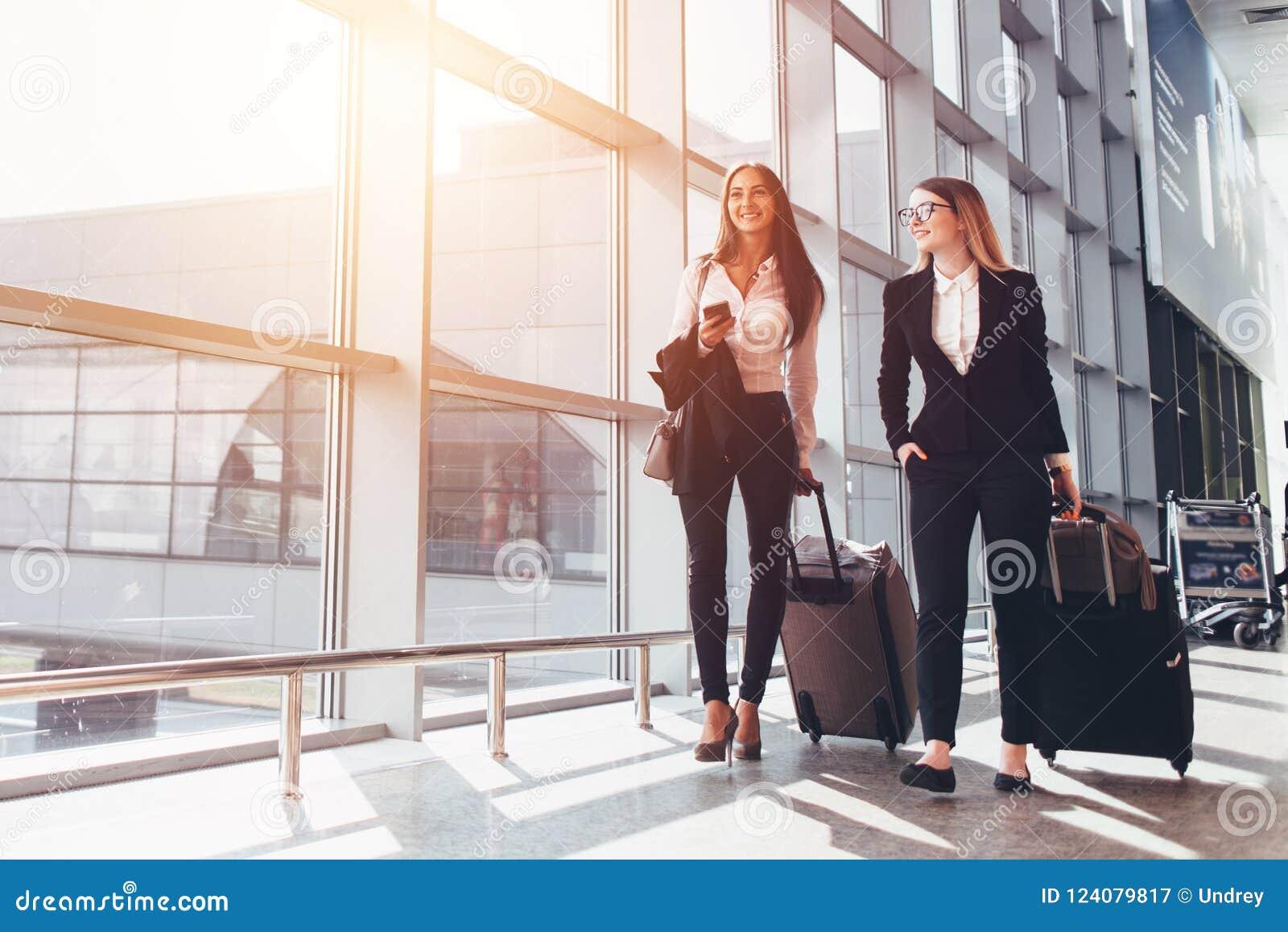 Dois sócios comerciais de sorriso que vão em malas de viagem levando da viagem de negócios ao andar através do corredor do aeropo