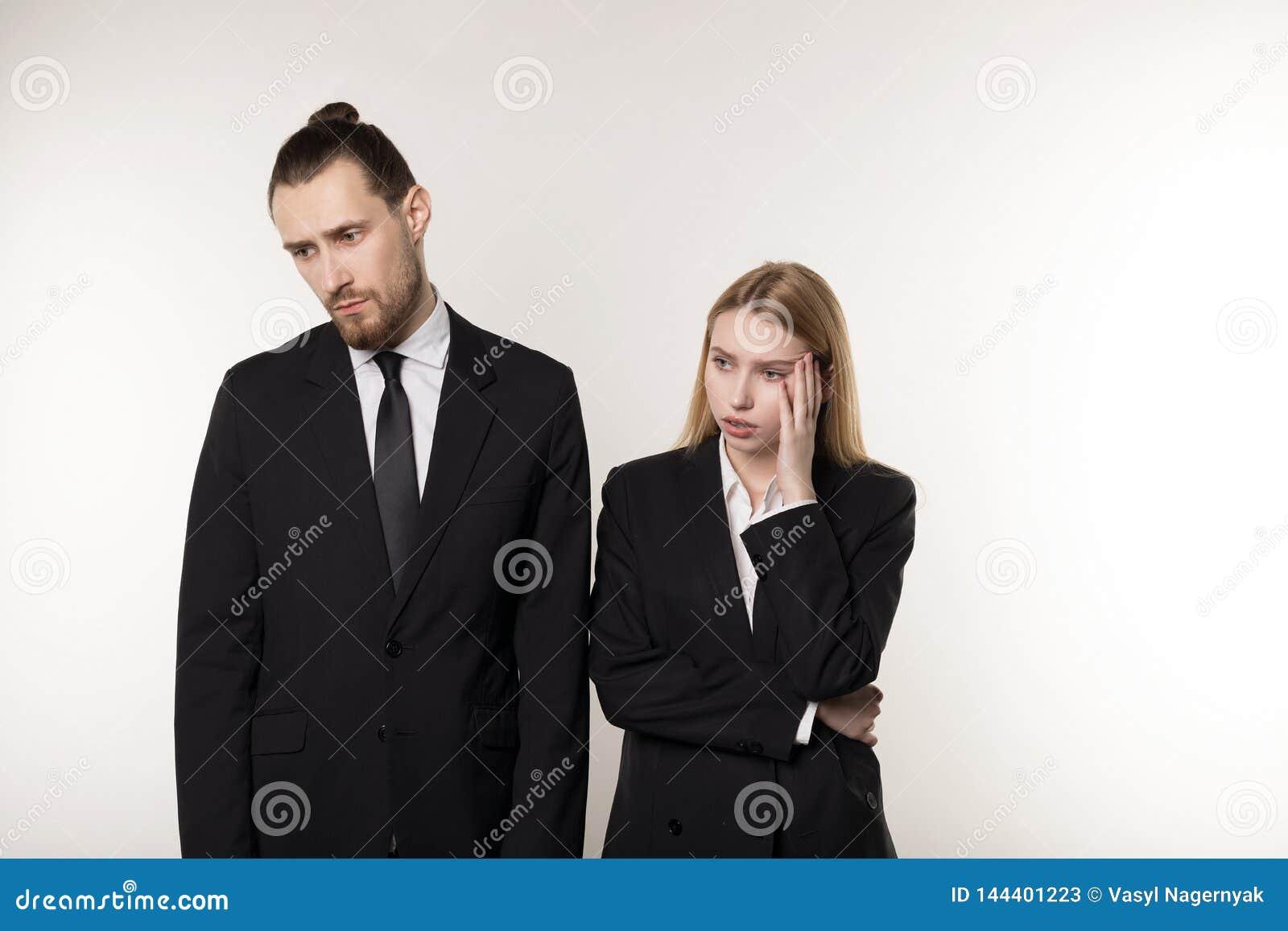 Dois sócios comerciais nos ternos pretos, no homem farpado considerável e na mulher loura bonita chocados não conhecem o que faze