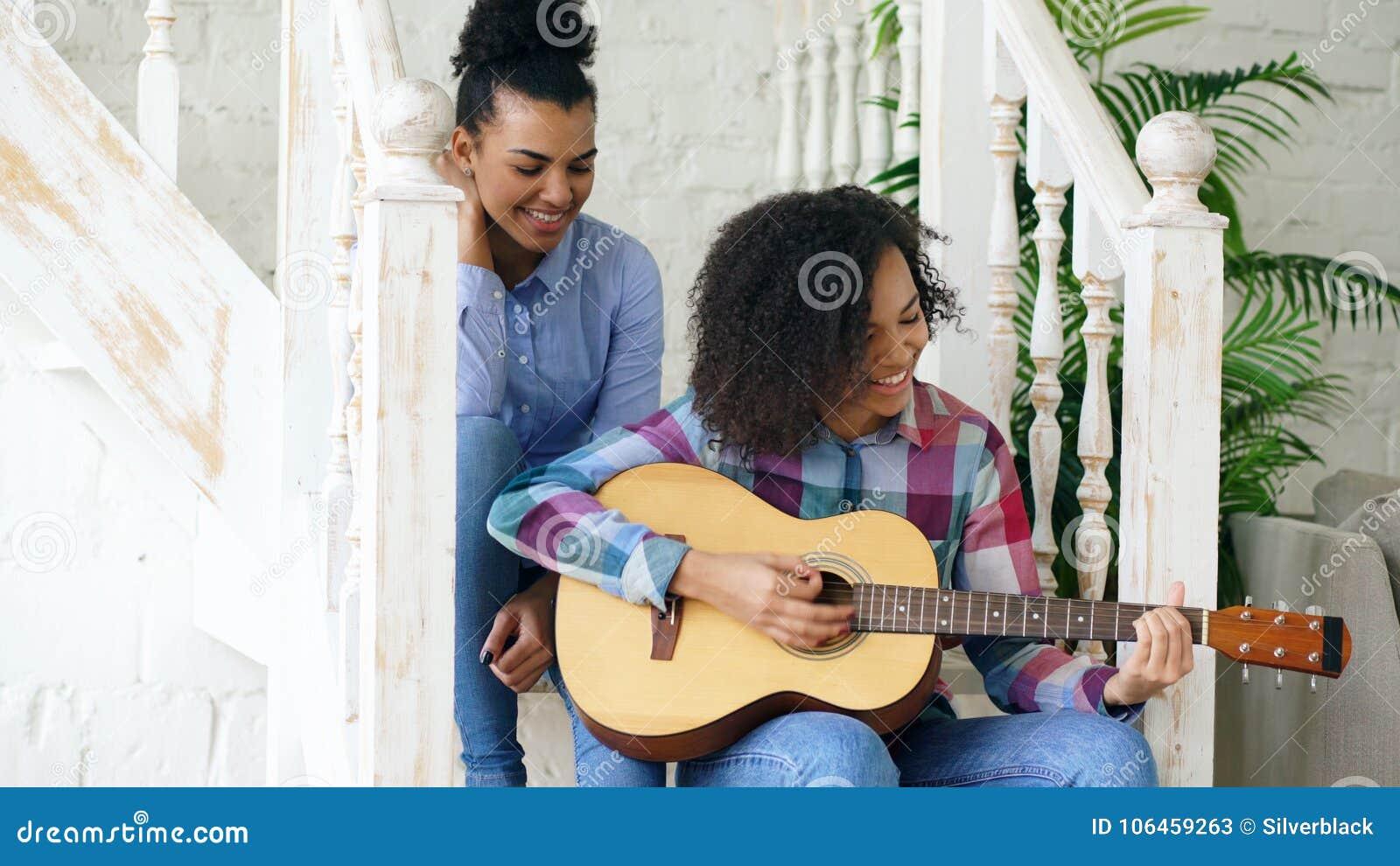 Dois sistres encaracolado brasileiros das meninas que sentam-se em escadas e prática jogar a guitarra acústica Os amigos têm o di