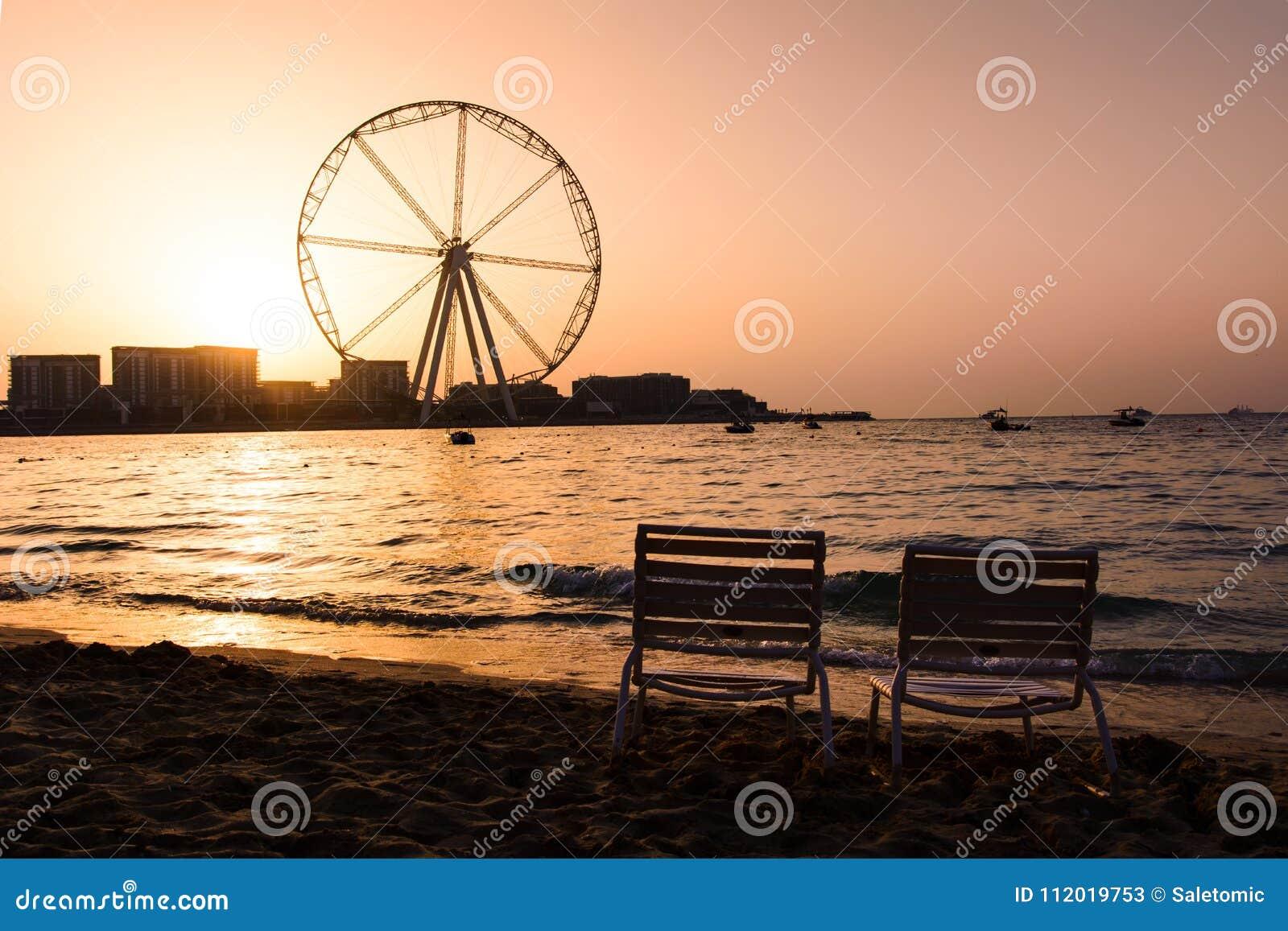 Dois sunbeds com opinião de roda de ferris de Ain Dubai em JBR encalham