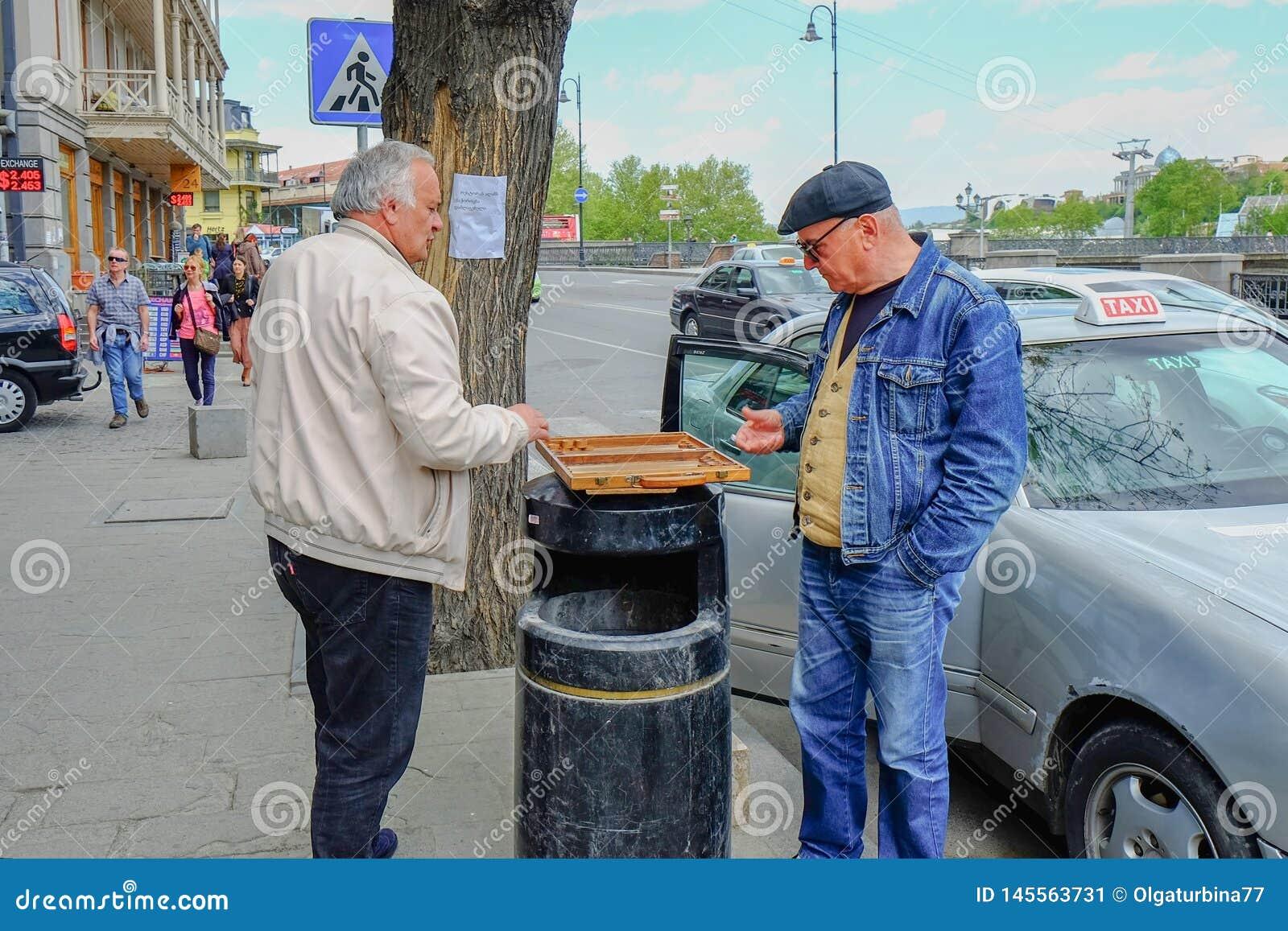 Dois taxistas idosos dos homens que jogam a gamão nos passageiros de espera da rua