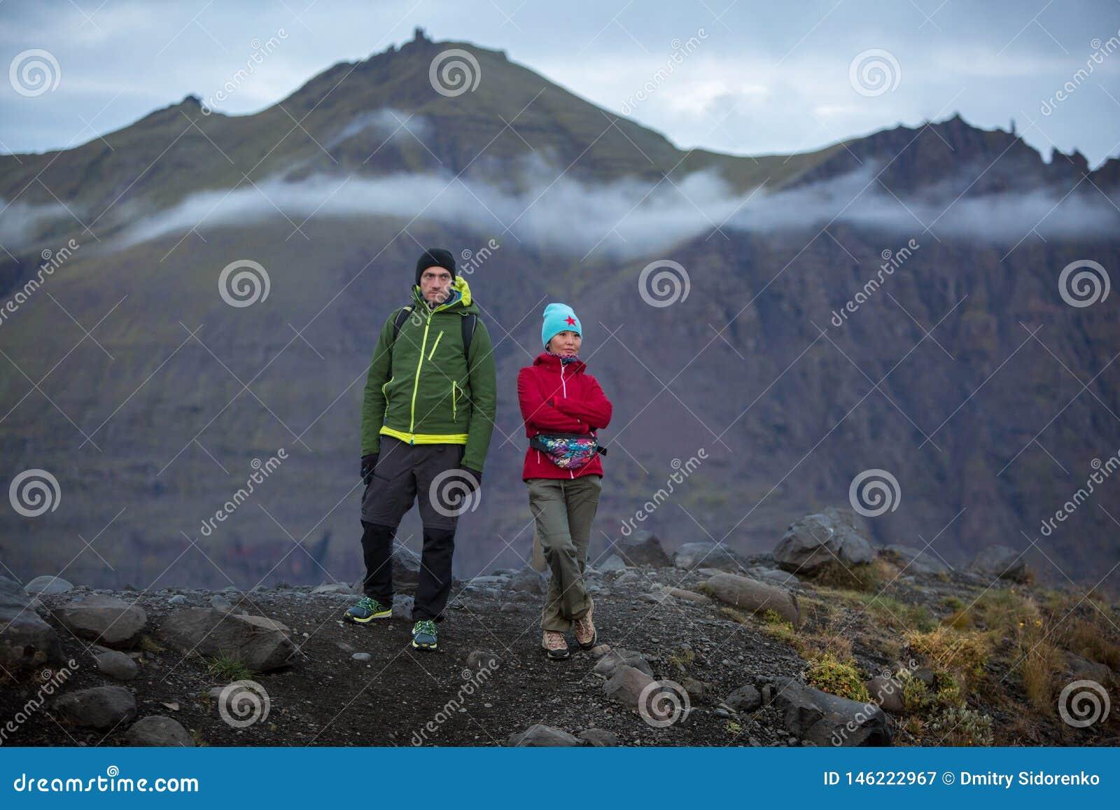 Dois turistas, um homem e uma mulher estão estando em um monte na perspectiva das montanhas vulcânicas