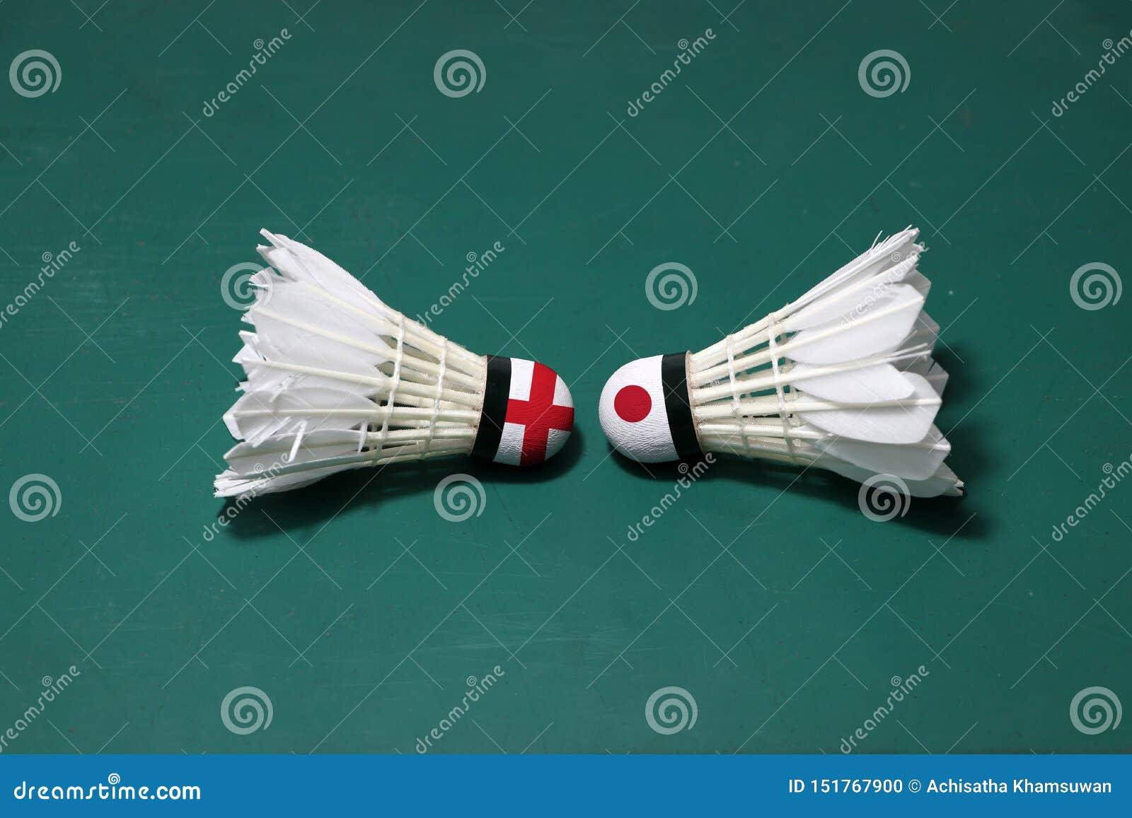 Dois usaram petecas no assoalho verde da corte de badminton com para dirigir-se Uma cabeça pintada com bandeira de Inglaterra e u