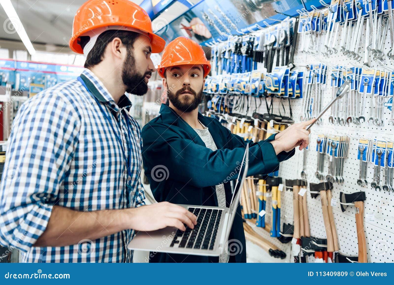 Dois vendedores estão verificando a seleção do equipamento na loja das ferramentas elétricas