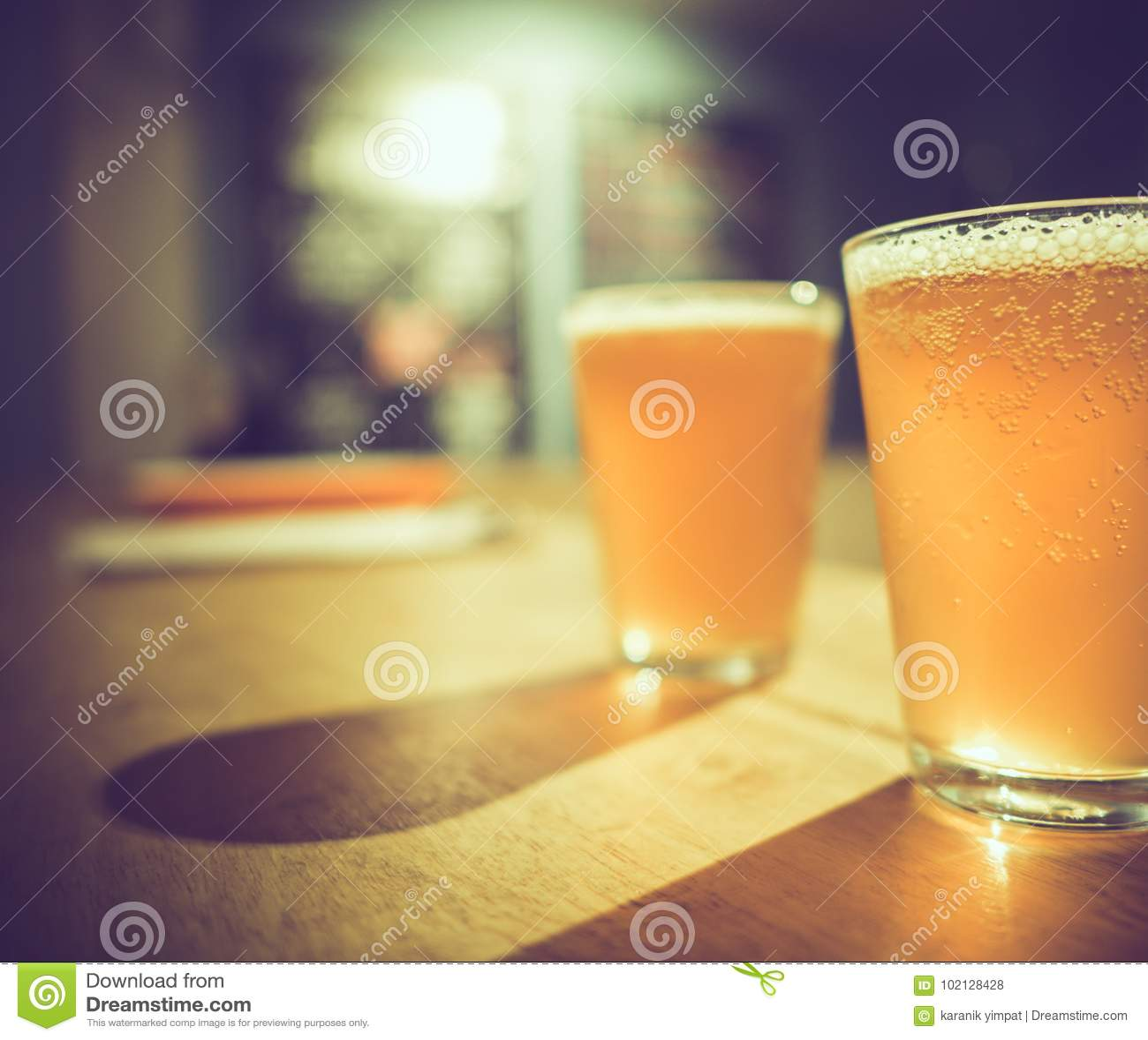 Dois vidros da cerveja fria do ofício com bolhas brancas e da sombra na tabela de madeira na barra, tom da obscuridade do vintage