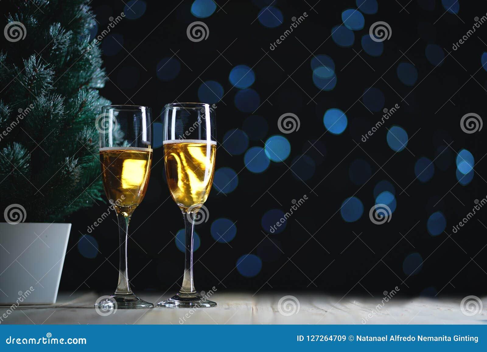Dois vidros de Champagne e do fulgor escuro pequeno Ligh da árvore de Natal