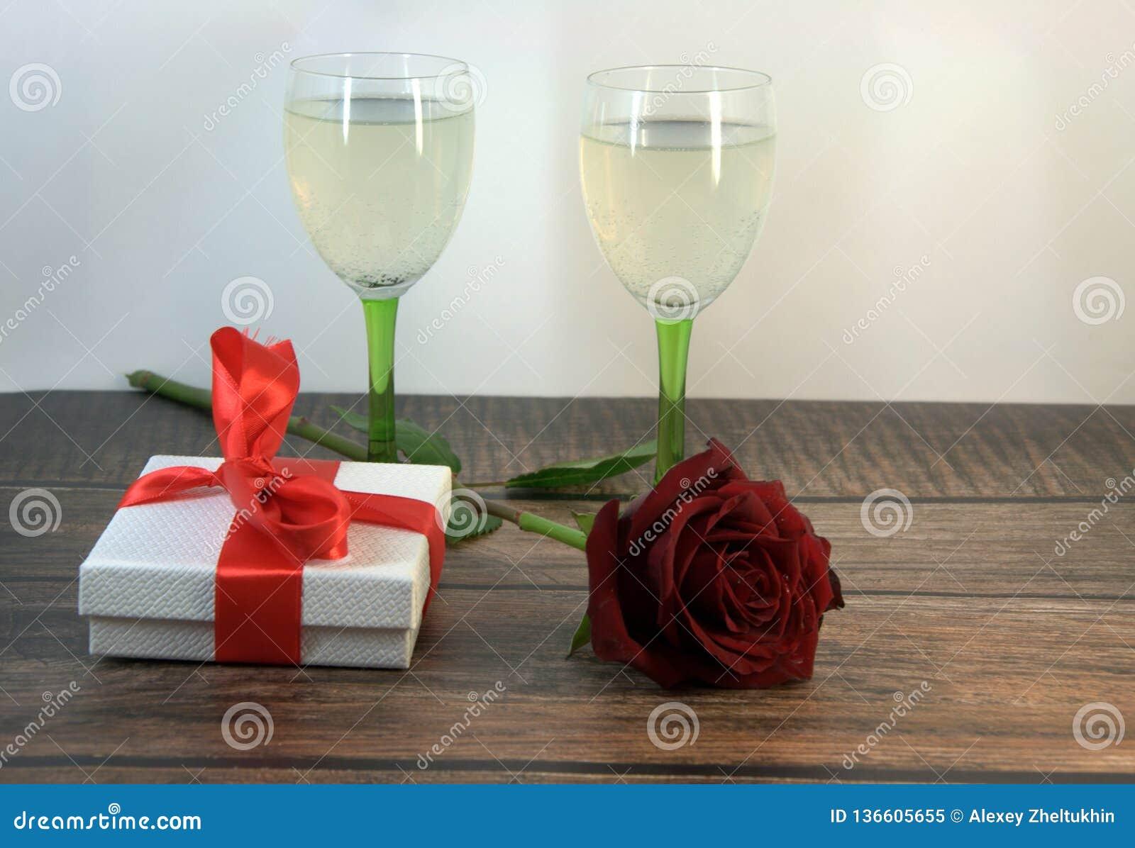 Dois vidros do champanhe, da rosa vermelha e da caixa de presente em uma tabela de madeira