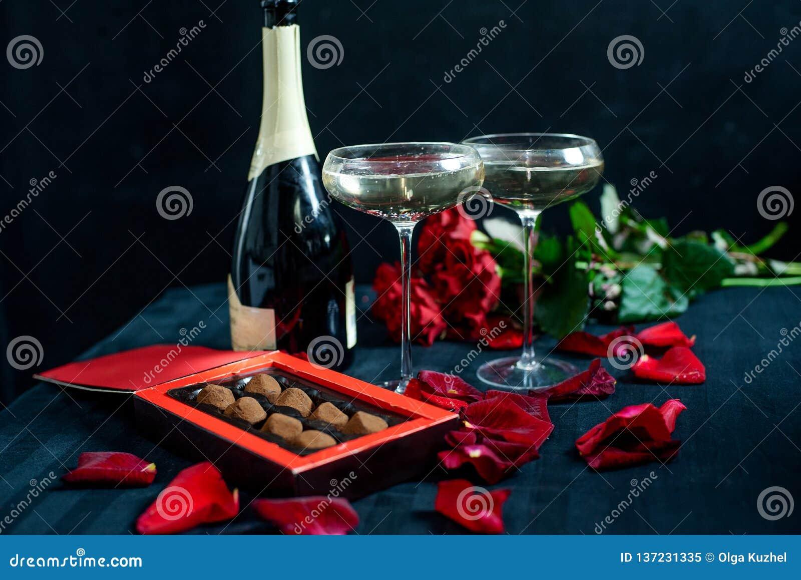 Dois vidros do champanhe, de rosas vermelhas, de pétalas e de chocolates em um fundo preto
