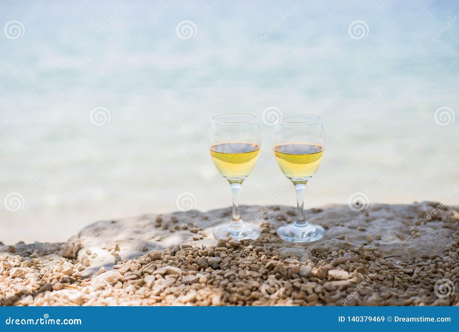 Dois vidros do vinho branco na praia com o mar no fundo