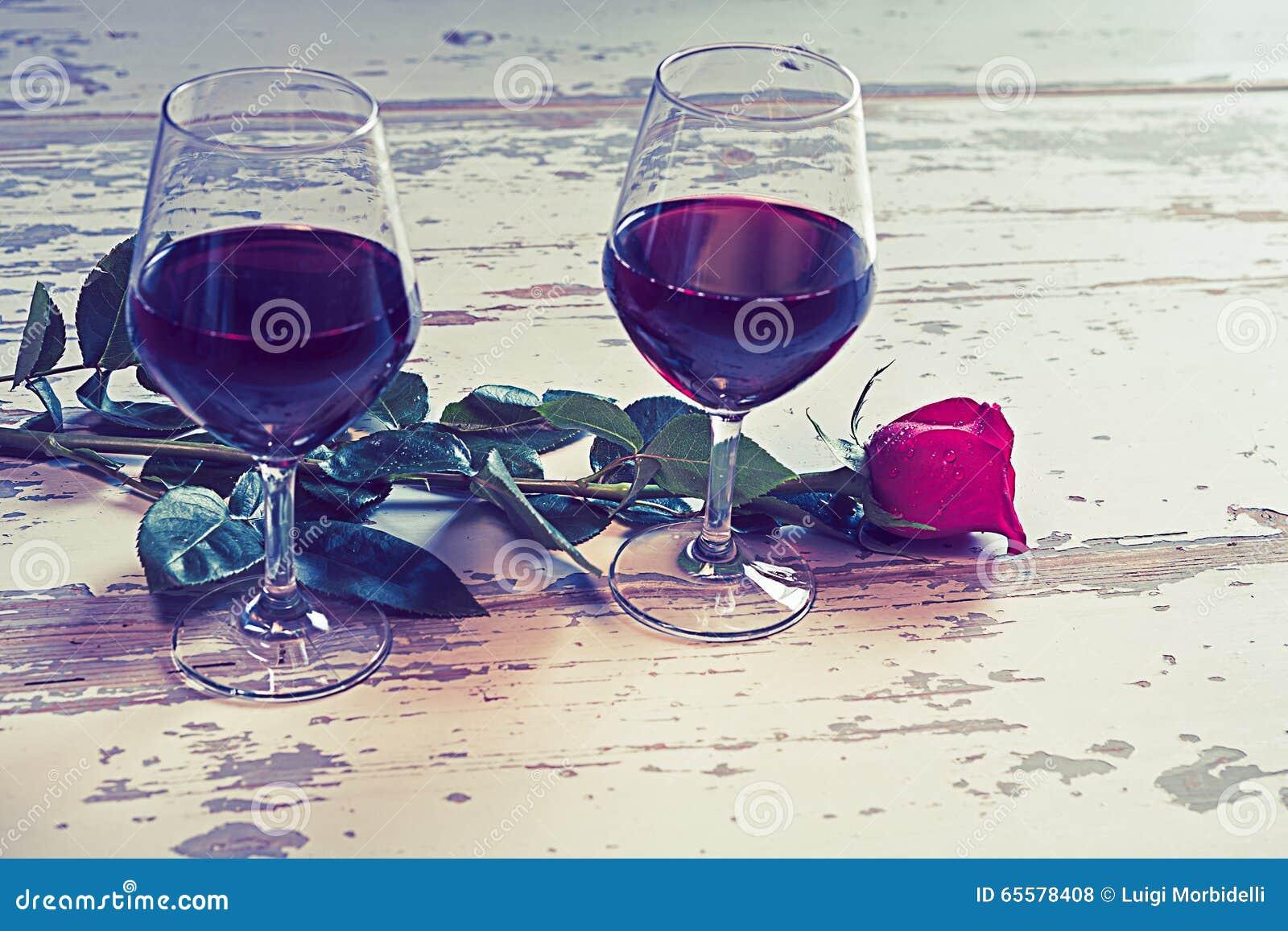 Dois vidros do vinho e de uma rosa vermelha