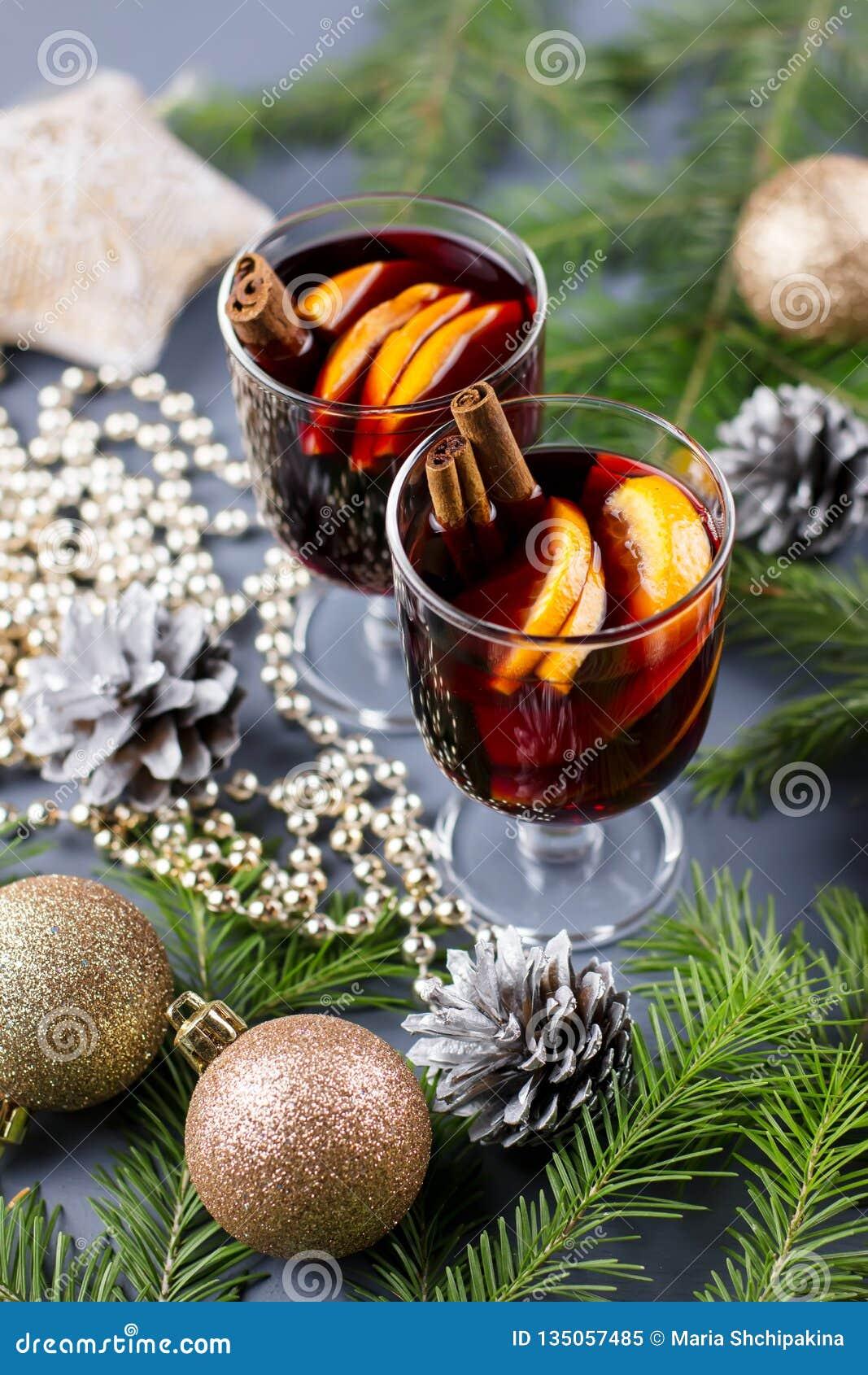 Dois vidros do vinho ferventado com especiarias quente com especiarias e a laranja cortada Bebida do Natal com vela e decorações