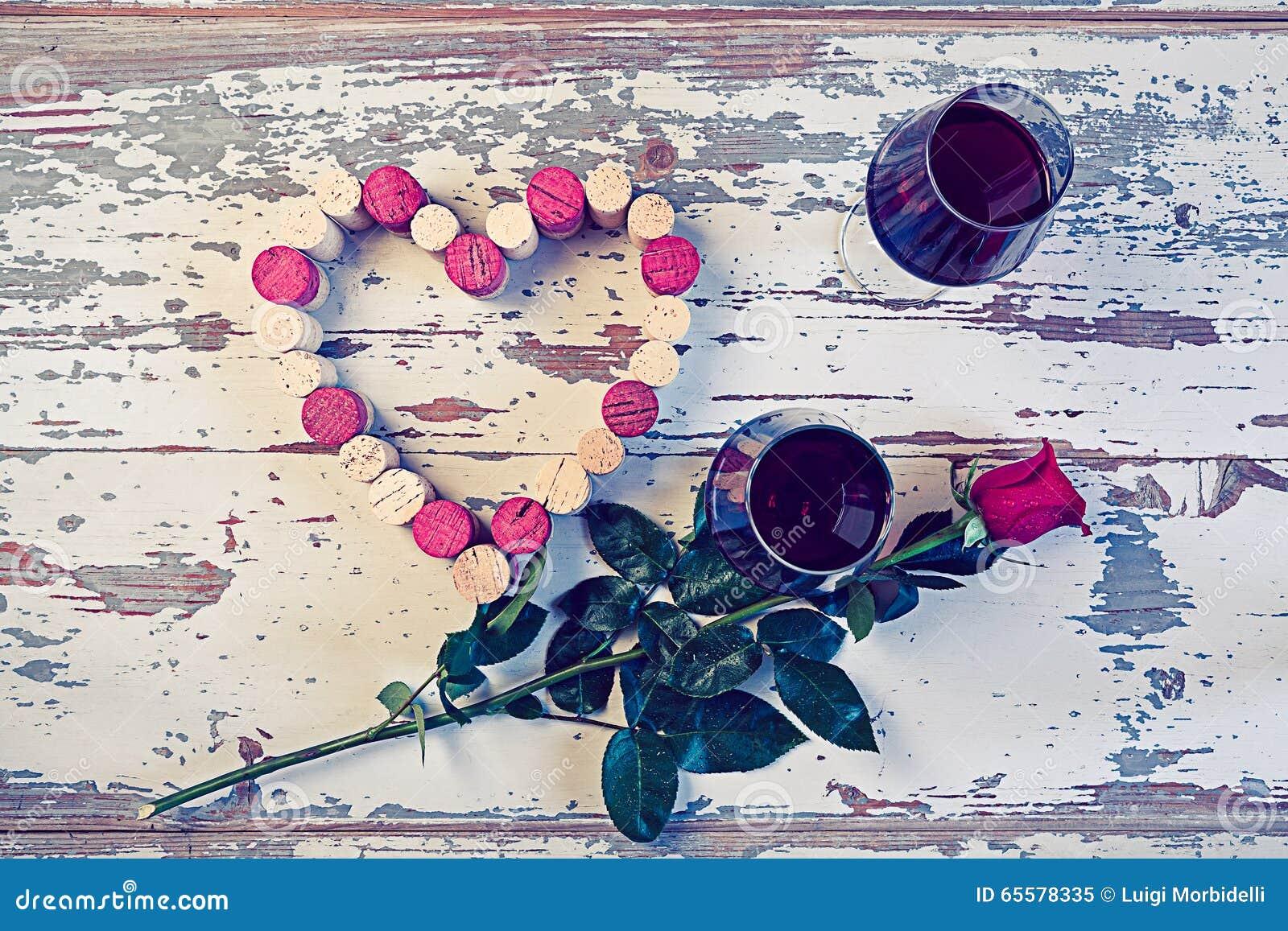 Dois vidros do vinho tinto e de um coração com cortiça
