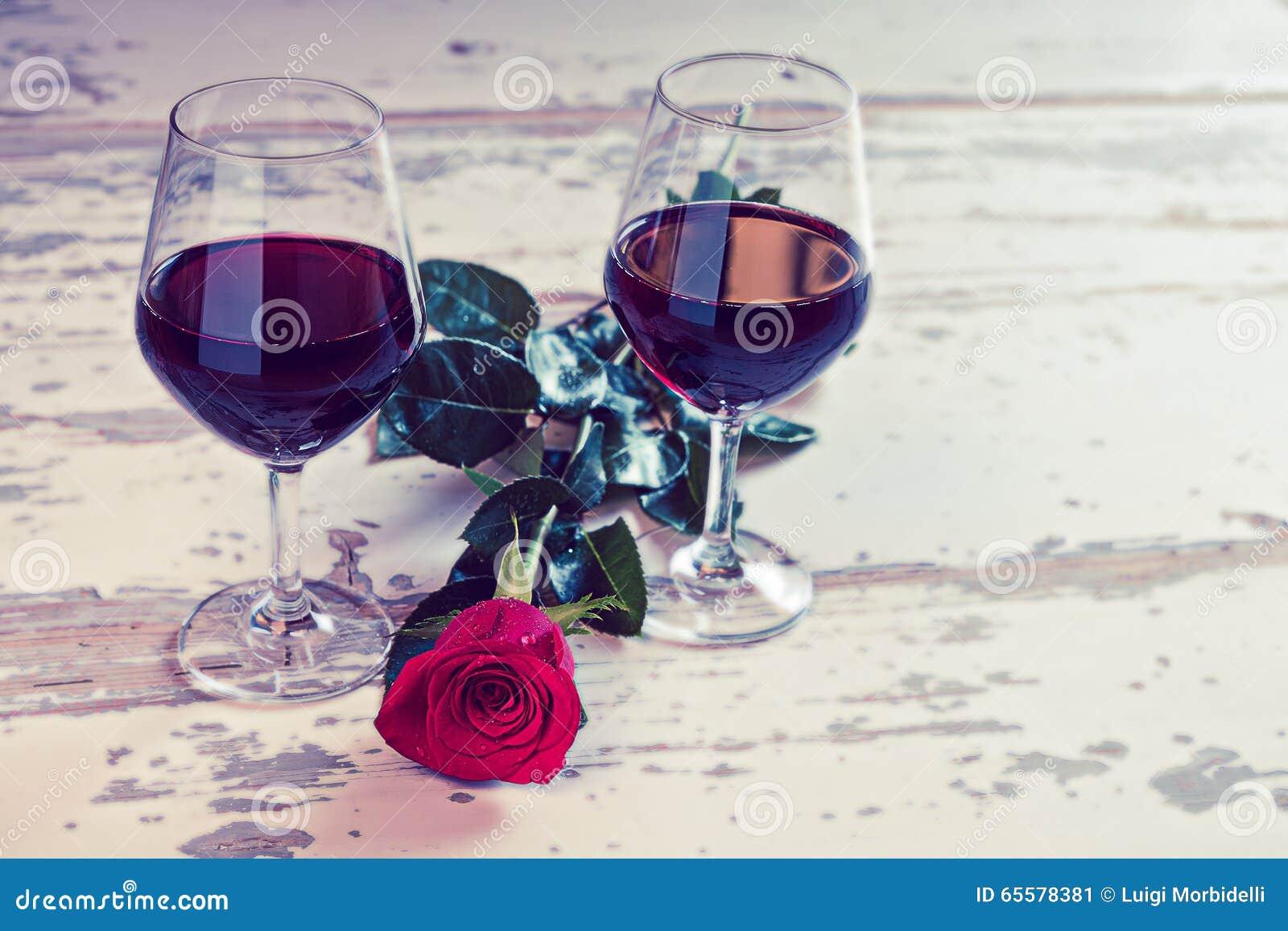 Dois vidros do vinho vermelho e de uma rosa