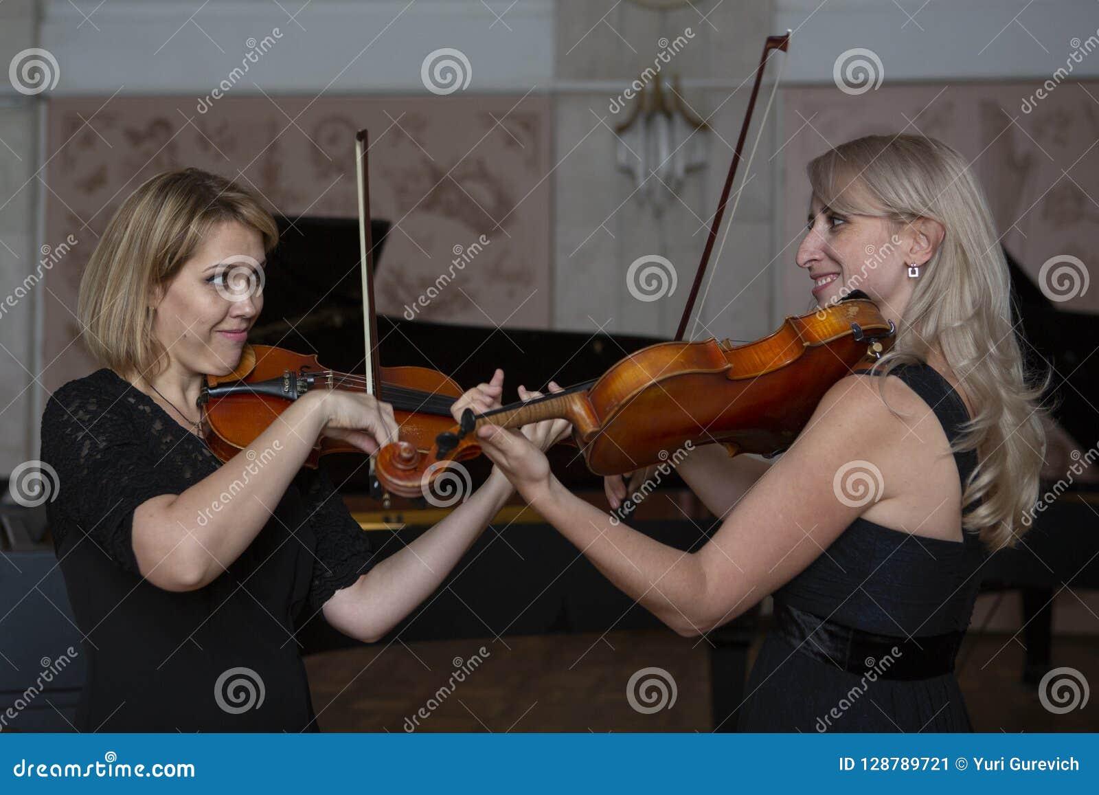 Dois violinistas fêmeas bonitos que jogam o violino