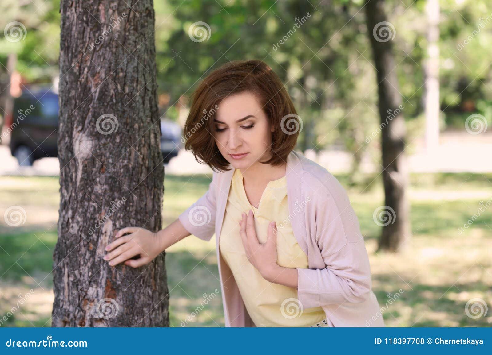 Dojrzała kobieta ma ataka serca blisko drzewa w zieleń parku