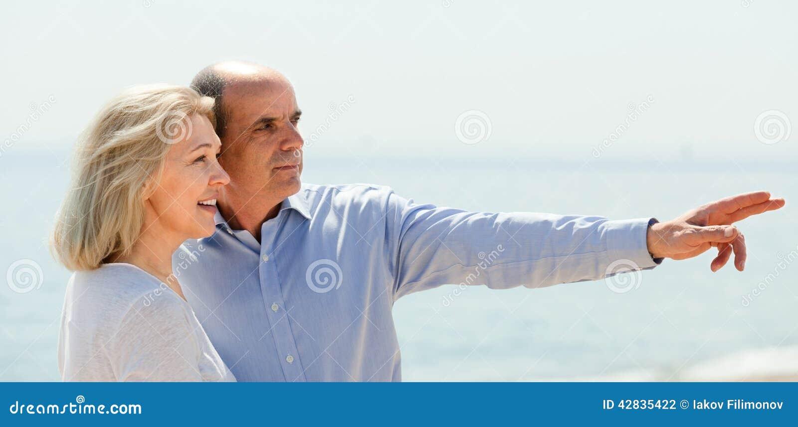 Dojrzała para wskazuje palce w przypadkowych ubraniach
