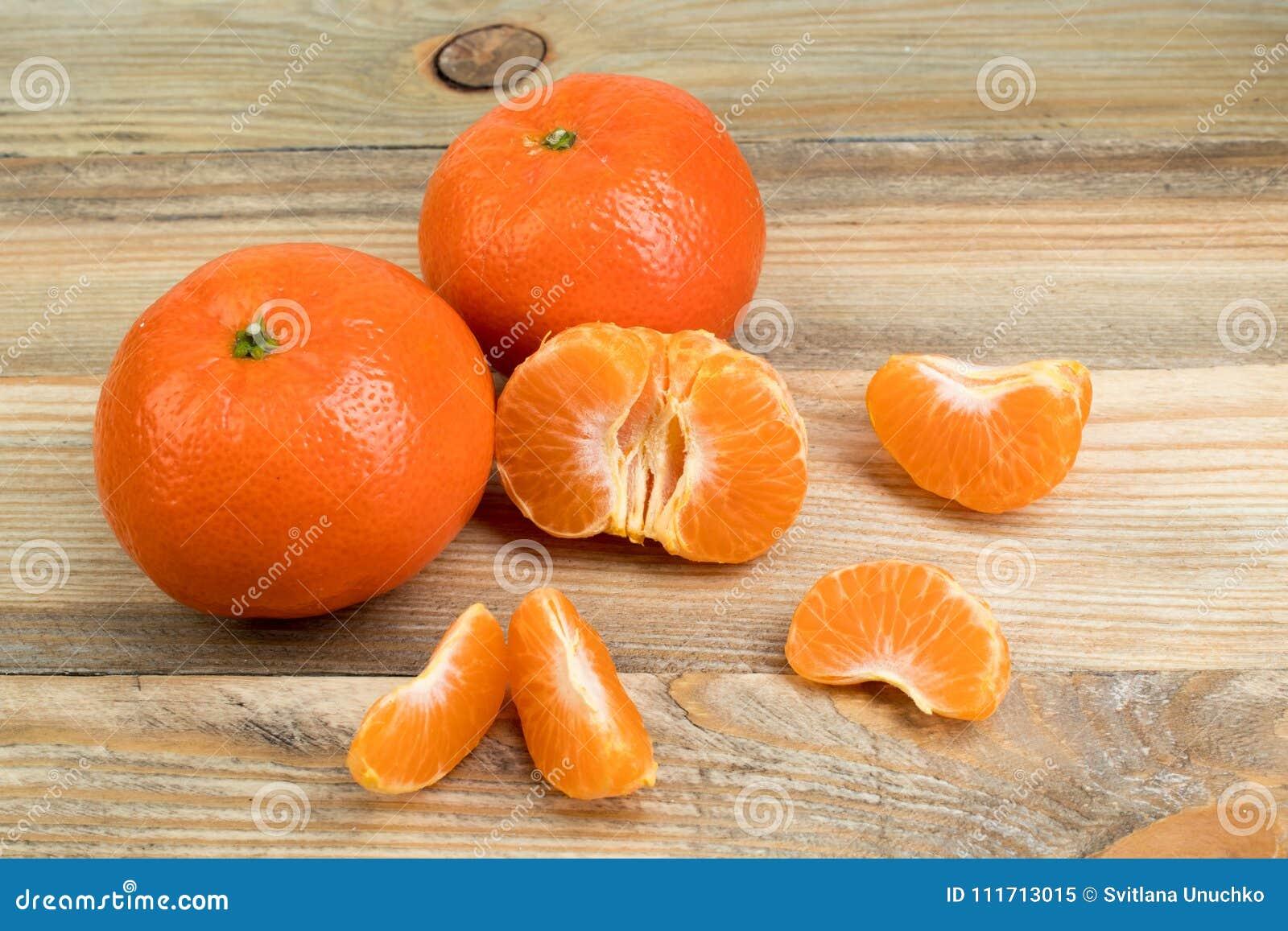 Dojrzała pomarańczowa świeża mandarynka, czysta mandarynka, mandarynka plasterki na drewnianym tle,