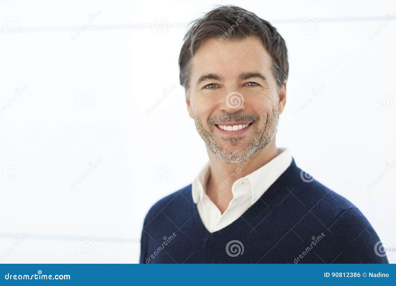 Dojrzały biznesmen ono Uśmiecha się Przy kamerą Odizolowywający na bielu