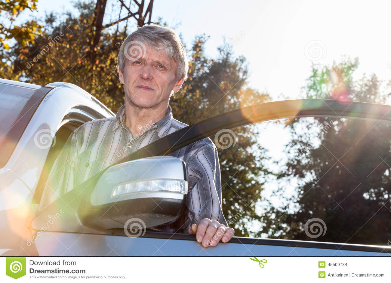 Dojrzały kierowca stoi blisko samochodu z rozpieczętowanym drzwi i światłem słonecznym na tle