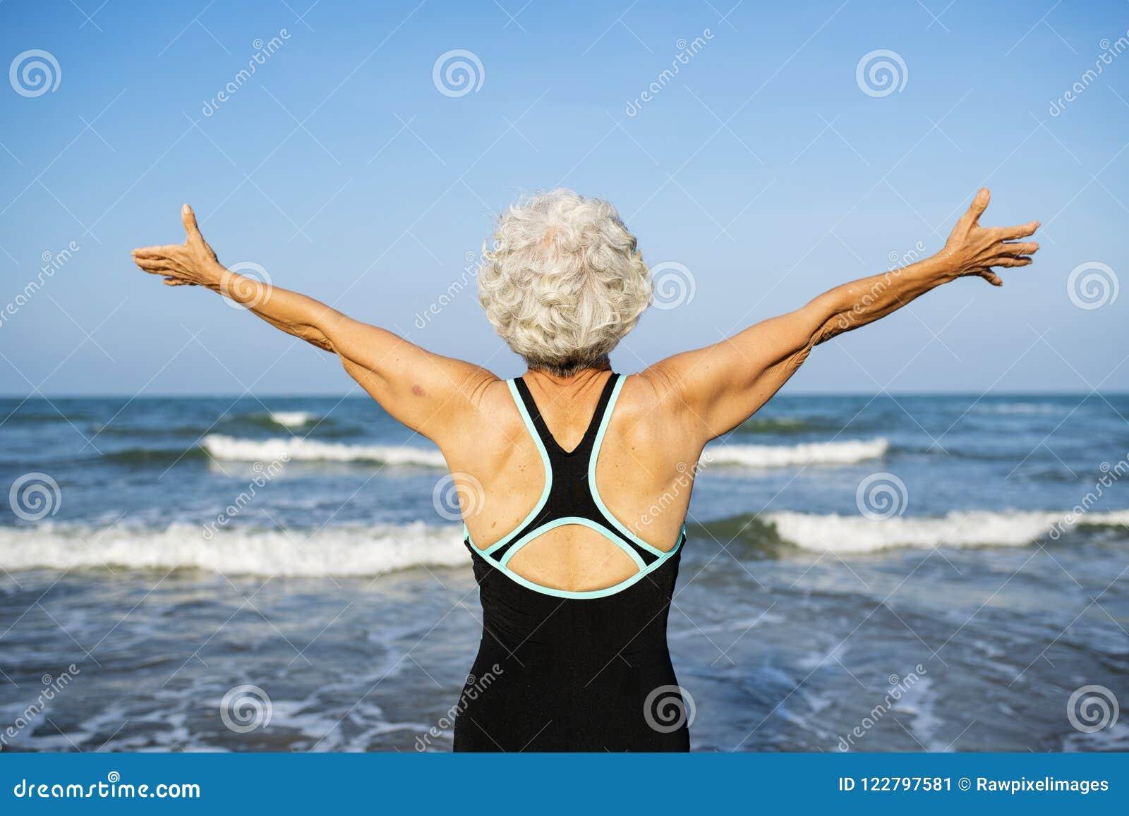 Dojrzały kobiety uczucie uwalnia przy plażą