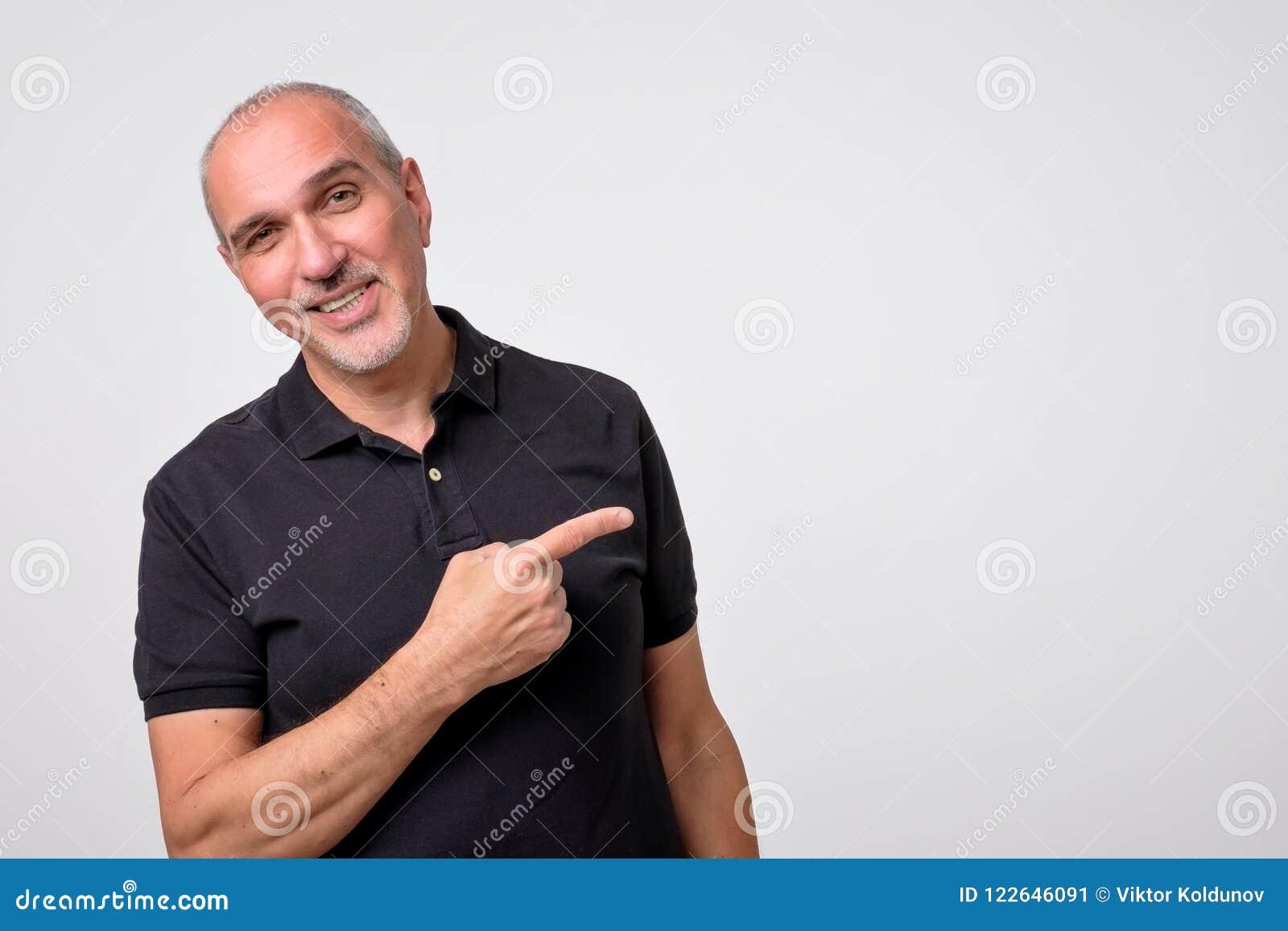Dojrzały latynoski mężczyzna wskazuje na boku odbitkową przestrzeń