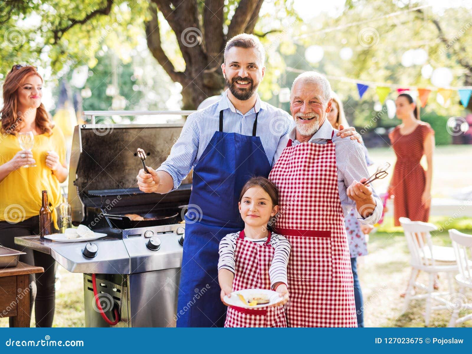 Dojrzały mężczyzna z rodziną i przyjaciółmi gotuje jedzenie na grilla przyjęciu