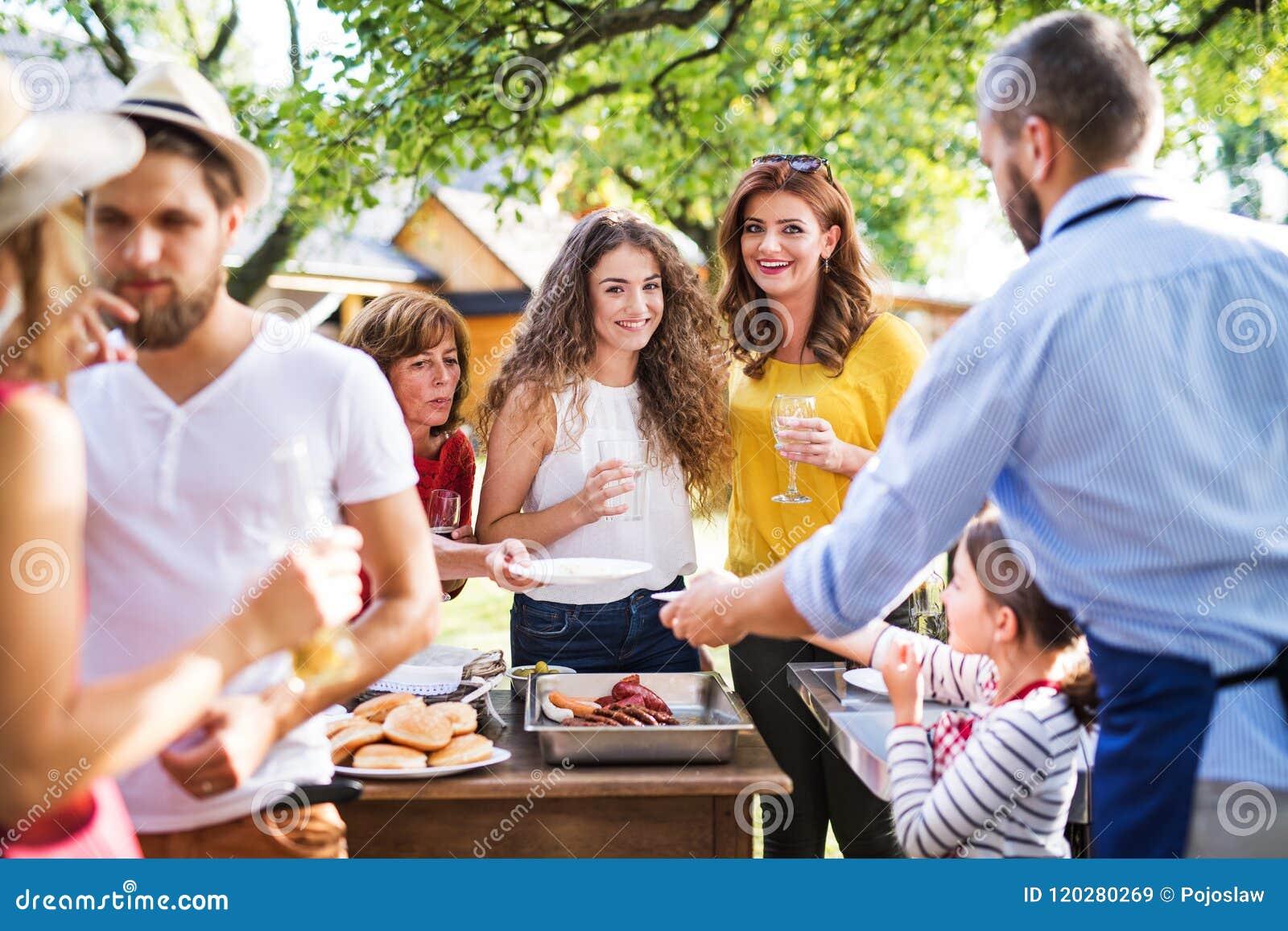 Dojrzały mężczyzna z rodziną i przyjaciółmi gotuje jedzenie na grillu na partyjnym outside
