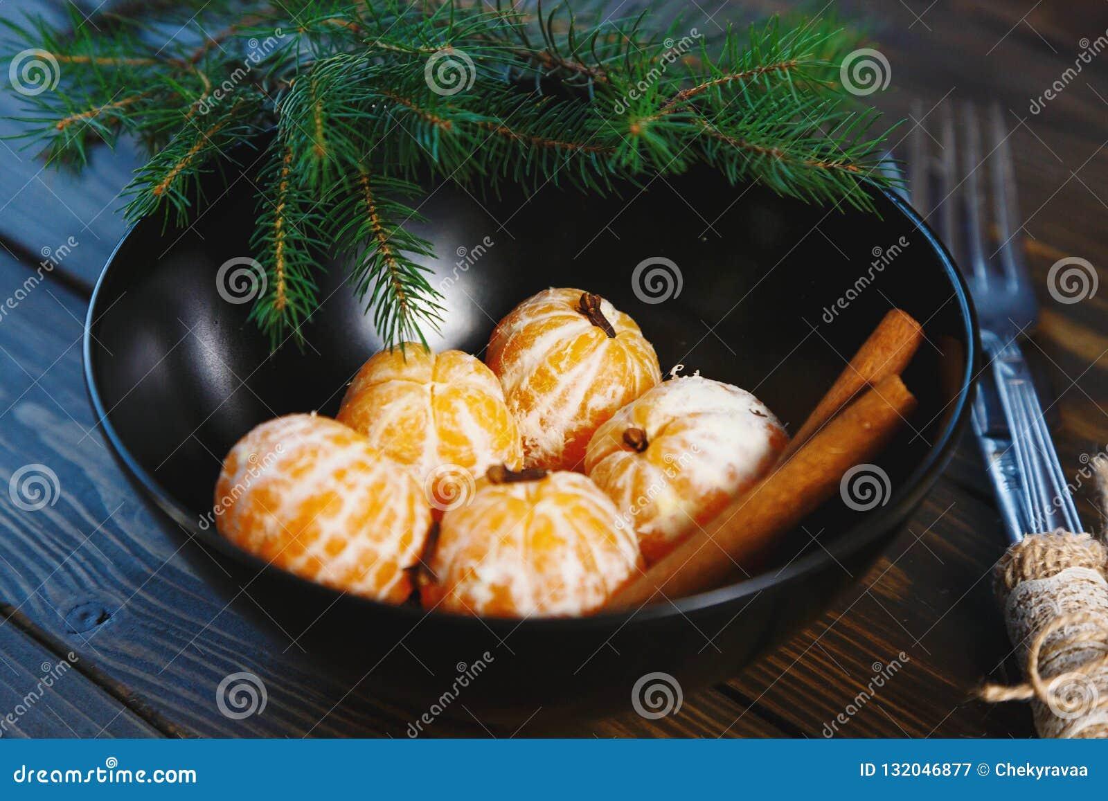 Dojrzały mandarine z liśćmi, tangerine mandarine pomarańcze w czarnym pucharze na drewnianym stołowym tle Cytrus owoc mandaryny w