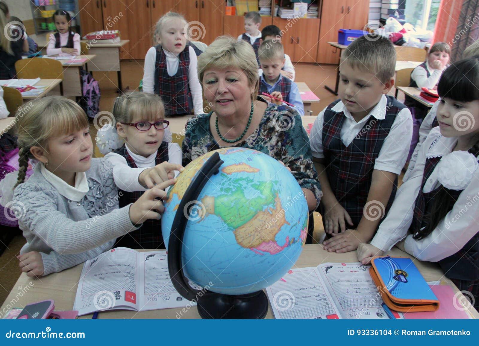 Dojrzały nauczyciel pokazuje kulę ziemską dzieci