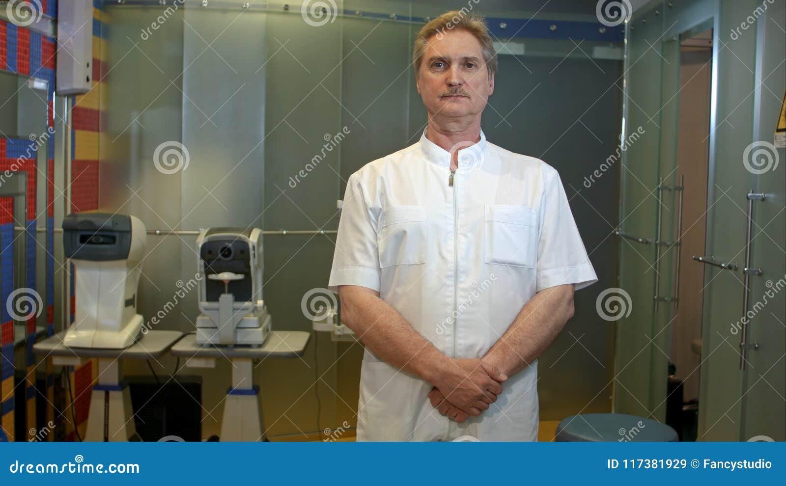 Dojrzały ophtolmologist patrzeje prosto naprzód z poważnym spojrzeniem na jego twarzy