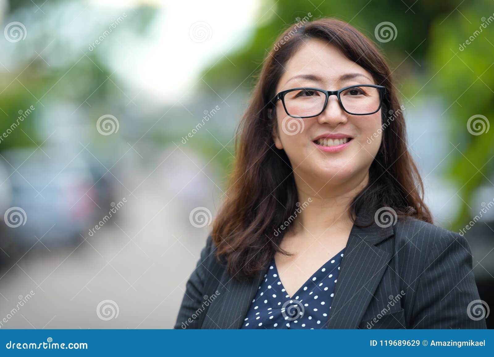 Dojrzały szczęśliwy piękny Azjatycki bizneswoman ono uśmiecha się outdoors i myśleć w ulicach