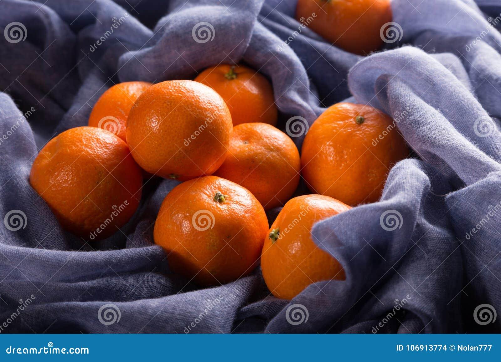 Dojrzali tangerines na błękitnej pielusze
