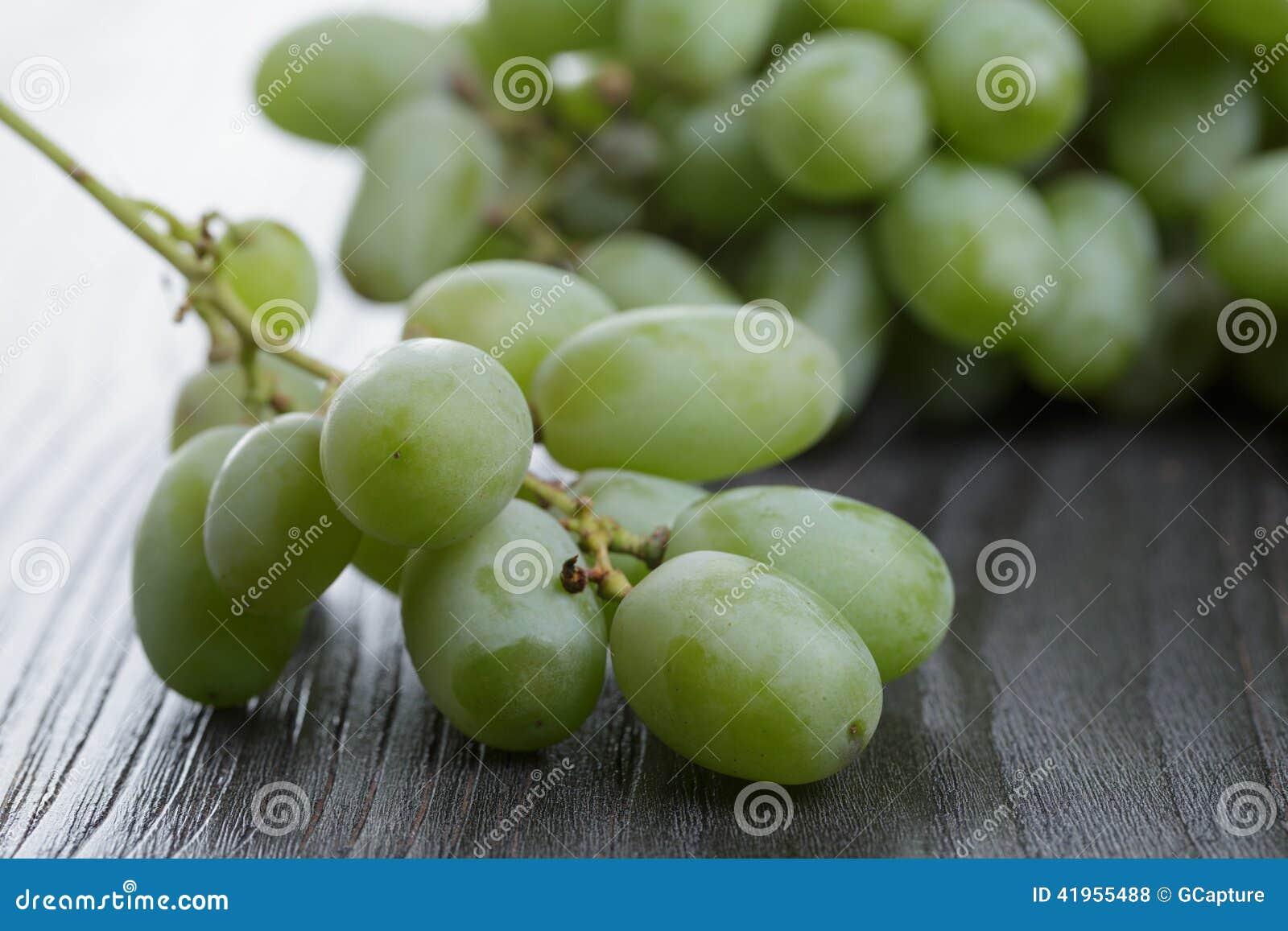 Dojrzali zieleni winogrona na czarnym drewno stole