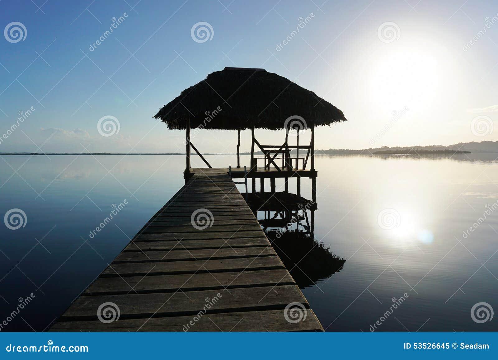 Dok met tropische hut over water op zonsopganglicht