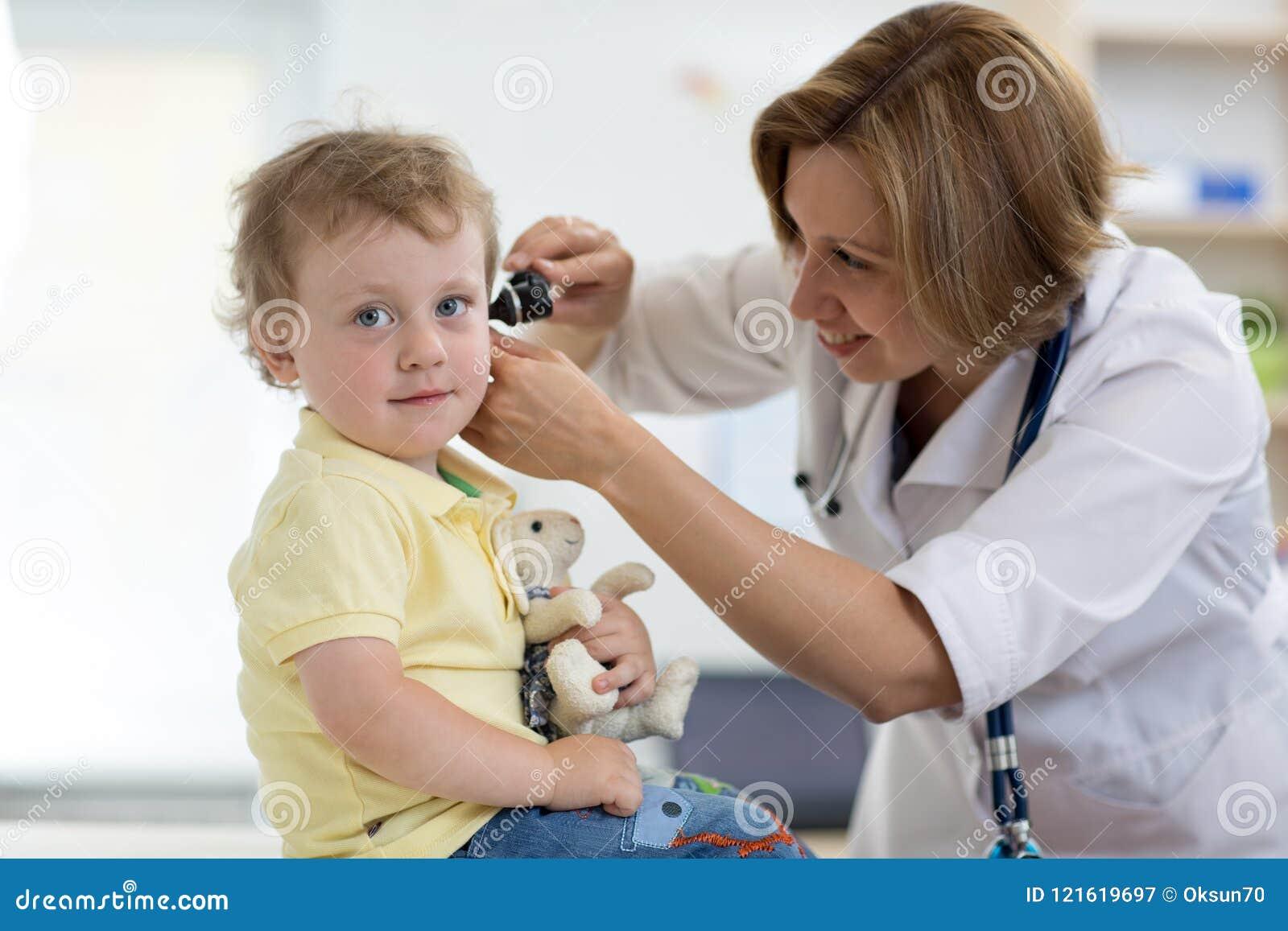 Doktor überprüft Ohr mit Otoscope in einem Kinderarztraum Medizinische Ausrüstung