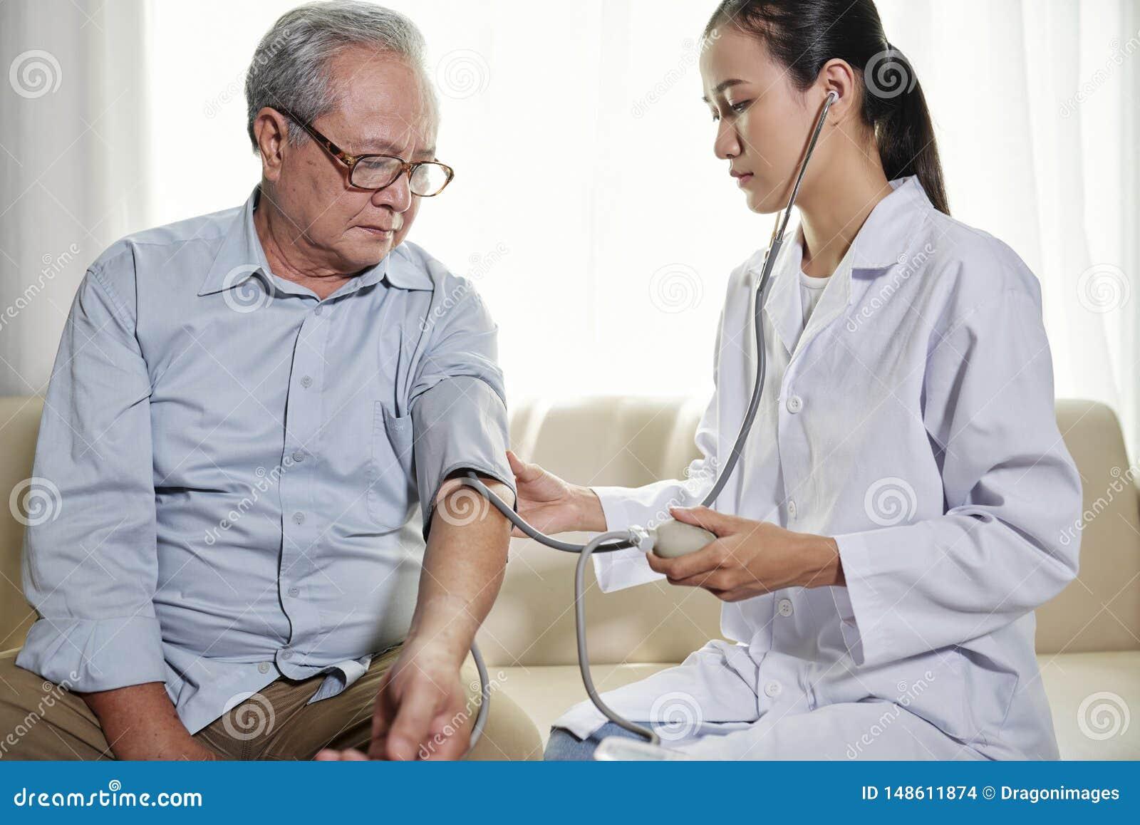 Doktor, der Blutdruck des Patienten ?berpr?ft