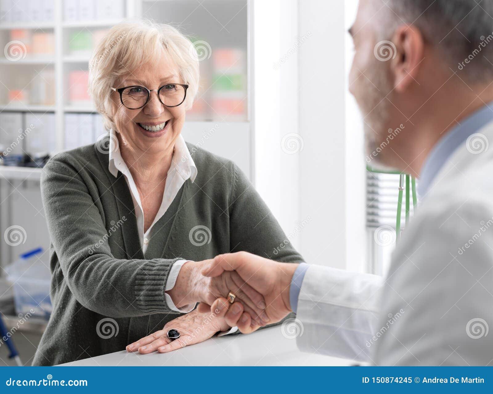 Doktor, der Hände mit einem älteren Patienten rüttelt
