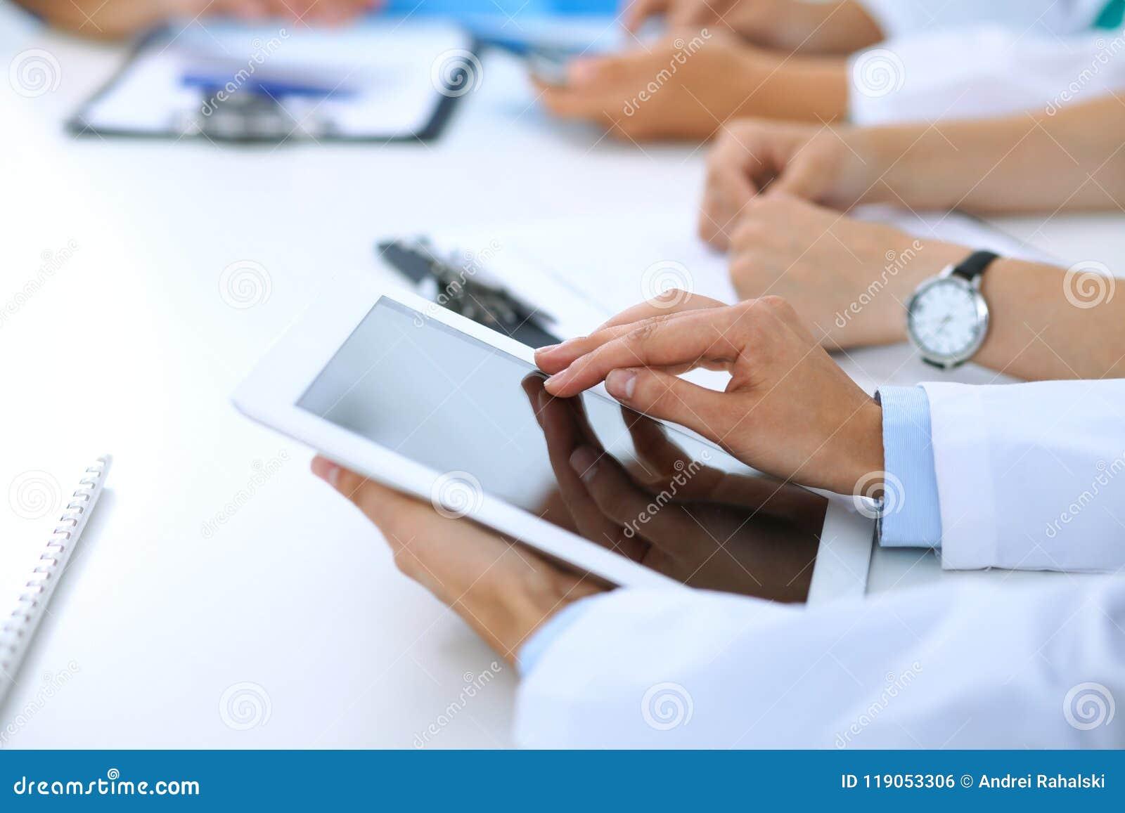 Doktor, der Tablet-Computer bei der medizinischen Sitzung, Nahaufnahme verwendet Gruppe Kollegen am Hintergrund