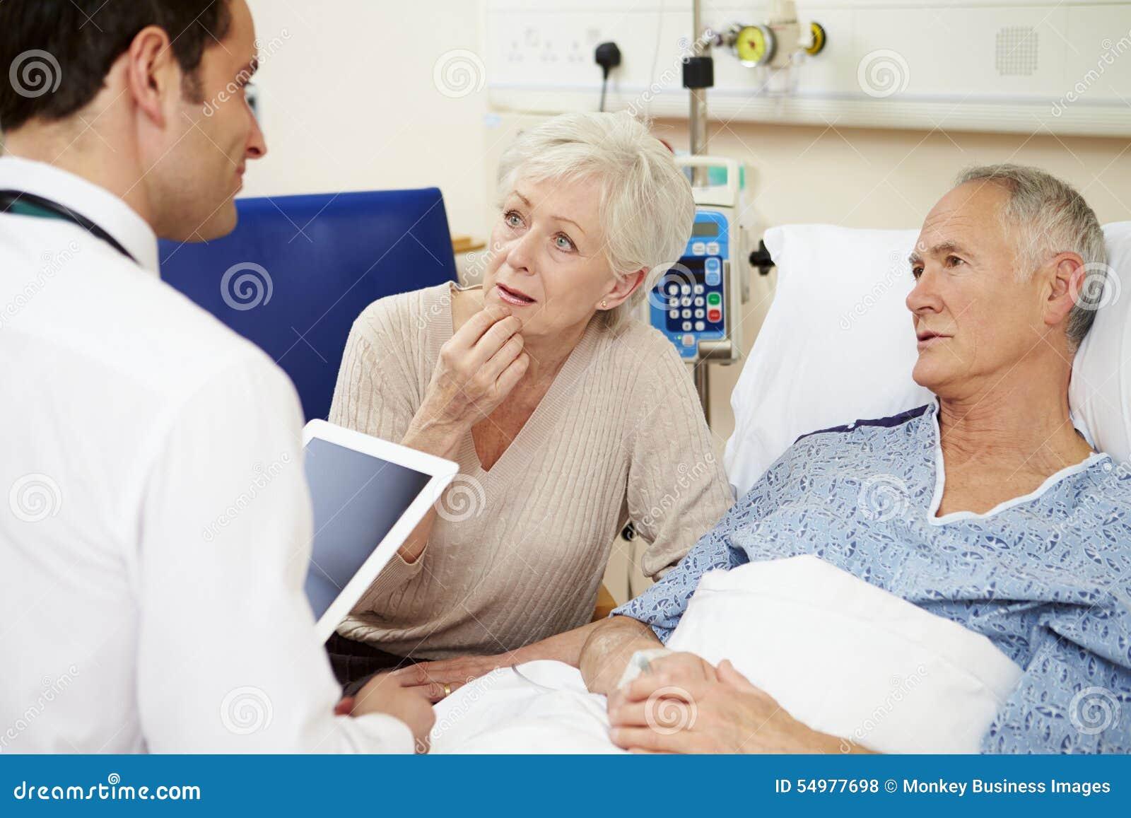 Doktor With Digital Tablet som talar till par vid sjukhussäng