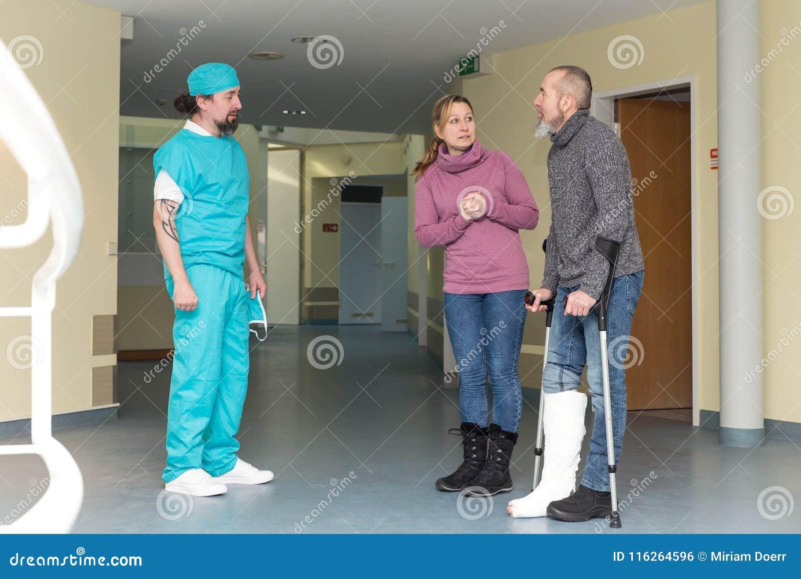 Doktor eller kirurg med patienten och kvinnan
