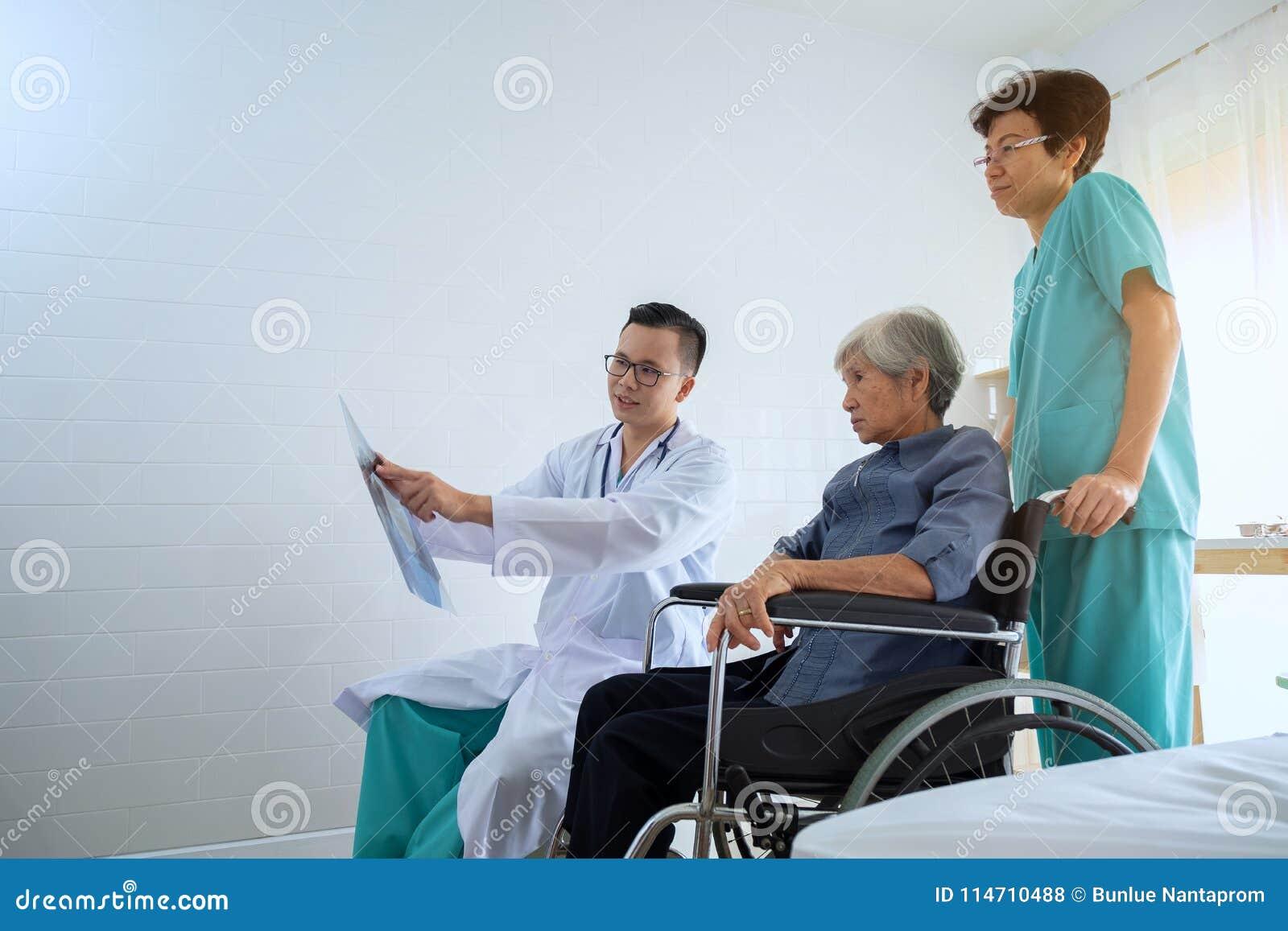 Doktor i kontoret som undersöker en röntgenstråle och diskuterar med en se