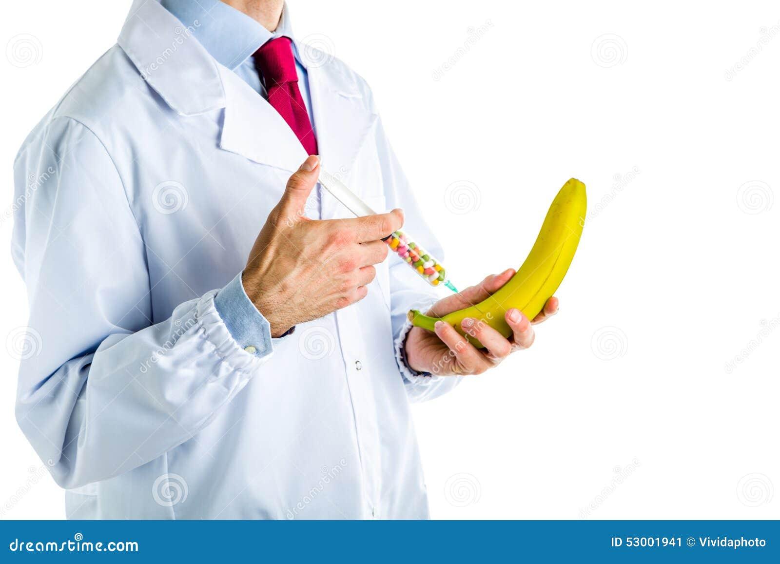 Doktor im weißen Mantel, der einer Banane eine Einspritzung macht