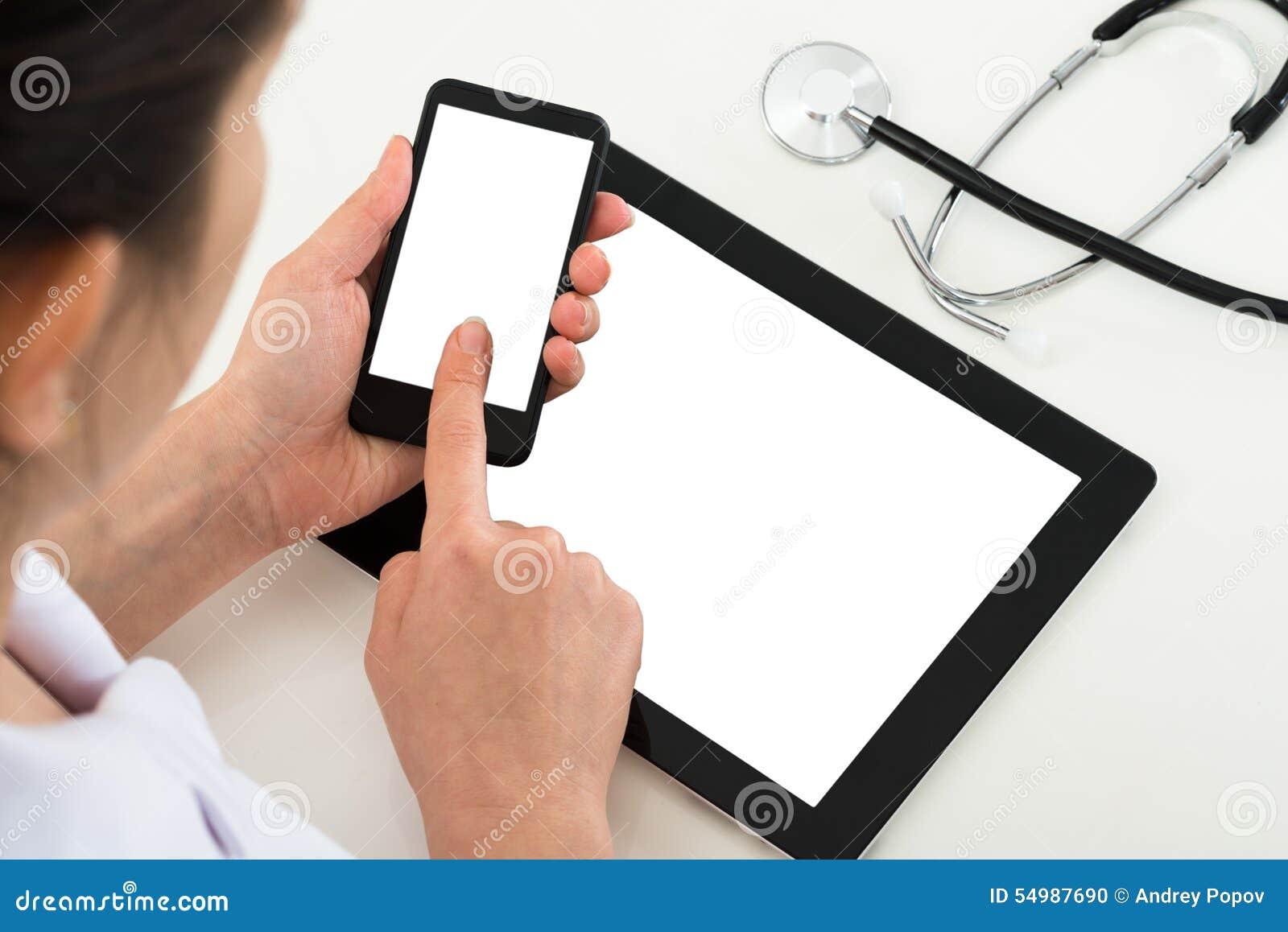 Doktor med mobiltelefonen för tom skärm och den digitala minnestavlan